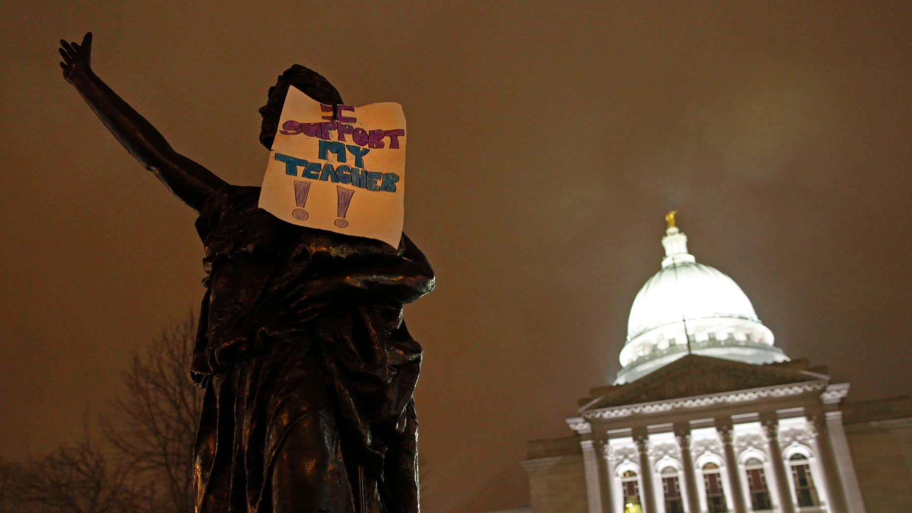 """February 21:  A sign that says """"I support my teacher"""" hangs on a statue outside the state Capitol in Madison, Wis. Twice as many public school teachers decided to retire this year as in each of the past two years."""