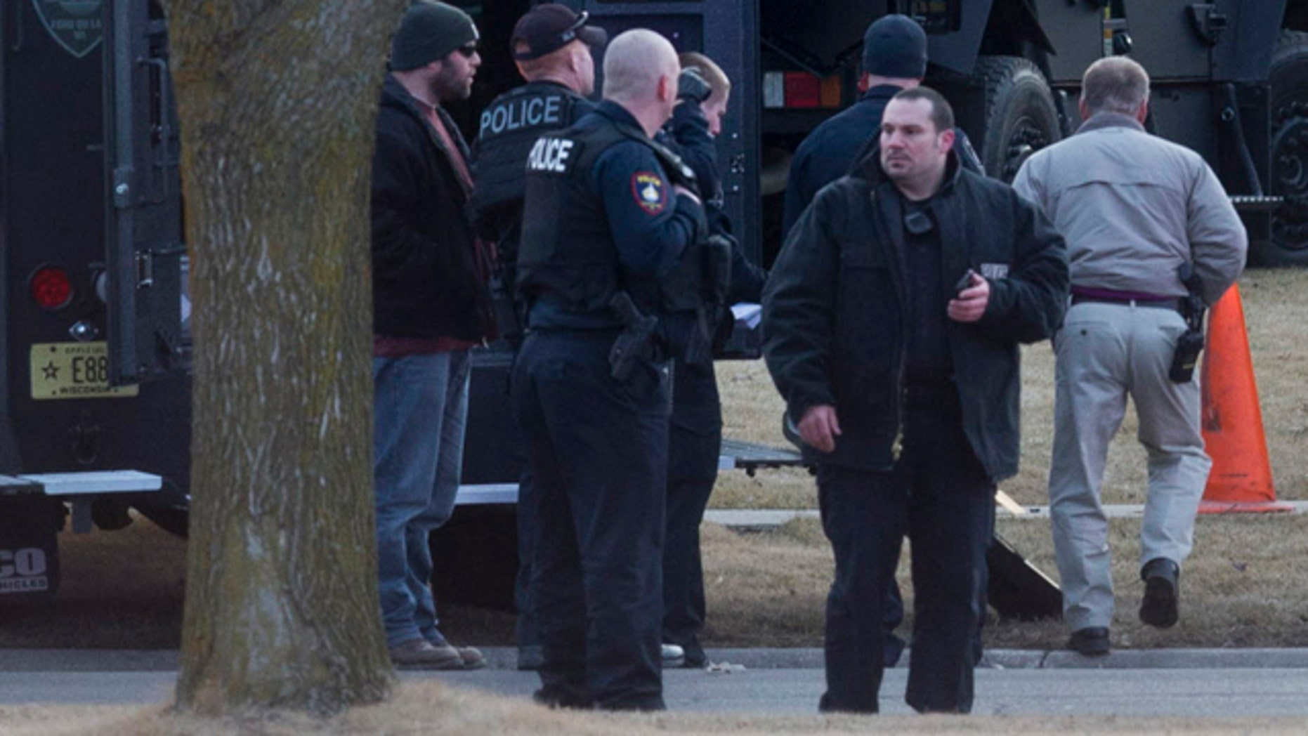 March 24, 2015: Law enforcement personnel gather at the scene of a shooting in Fond du Lac, Wis. Authorities say a Wisconsin state trooper was shot and killed in an exchange of gunfire with a person who matched the description of a bank robbery suspect. Police said the suspect also was killed. (AP Photo/Milwaukee Journal-Sentinel, Mark Hoffman)