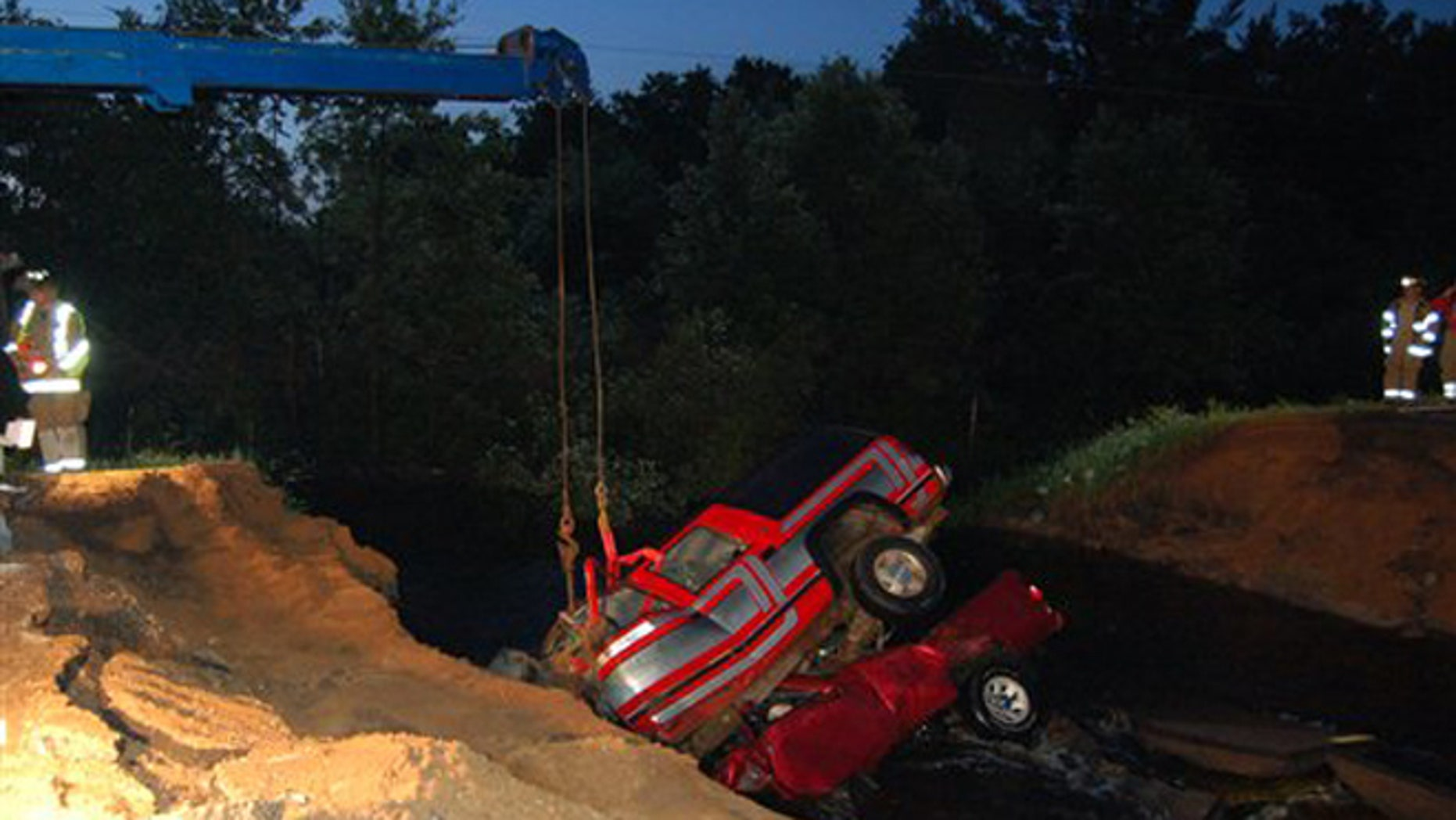 June 20, 2012: Clark County Sheriffs deputies watch as two vehicles are extracted from a washout hole after they crashed in to the large hole created by heavy rains, killing three people, on county road M near Neillsville, Wis.