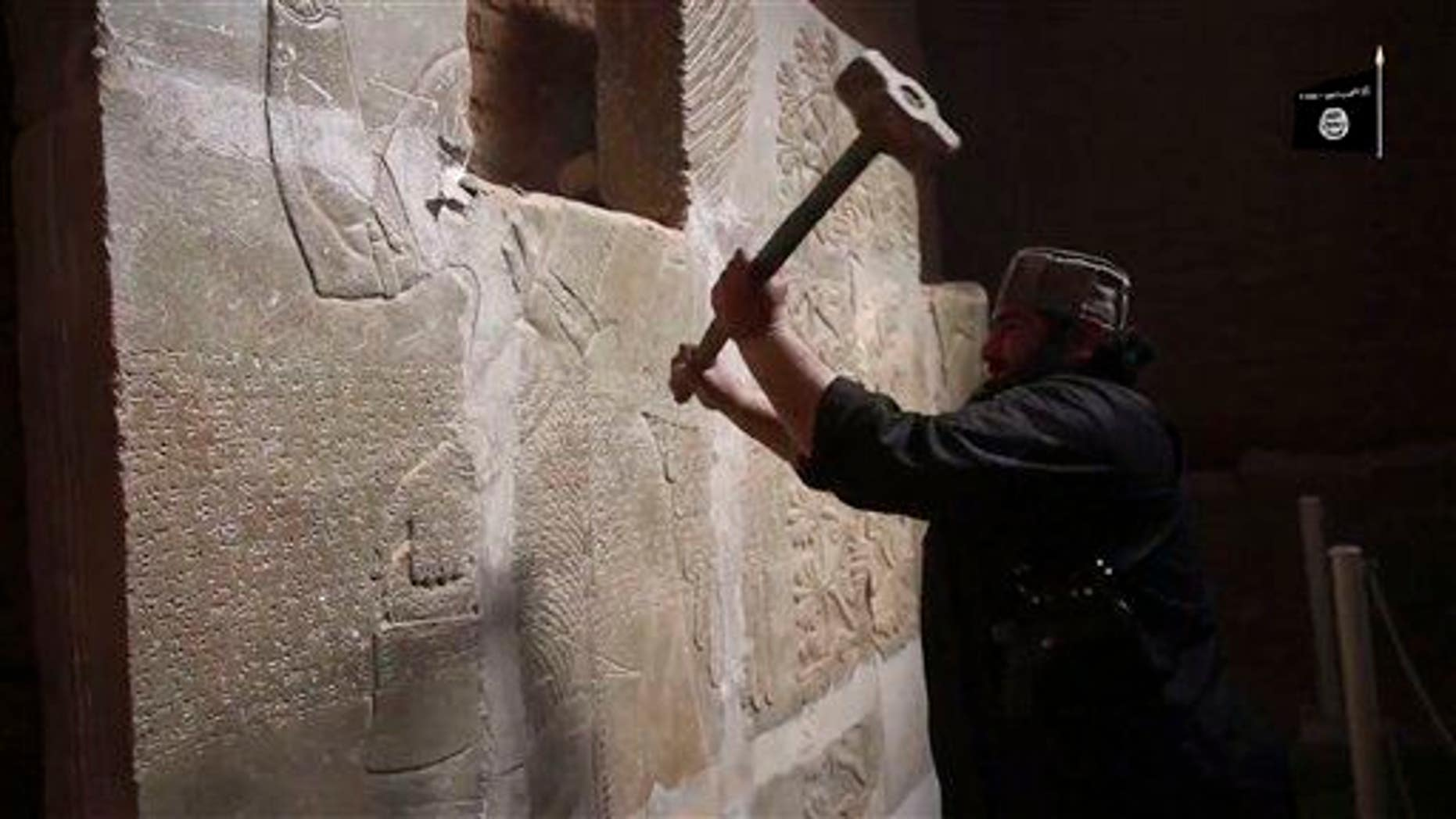 This image made from an apparent ISIS video posted April 11, 2015, purports to show a militant taking a sledgehammer to an Assyrian relief at the site of the ancient Assyrian city of Nimrud in Iraq.