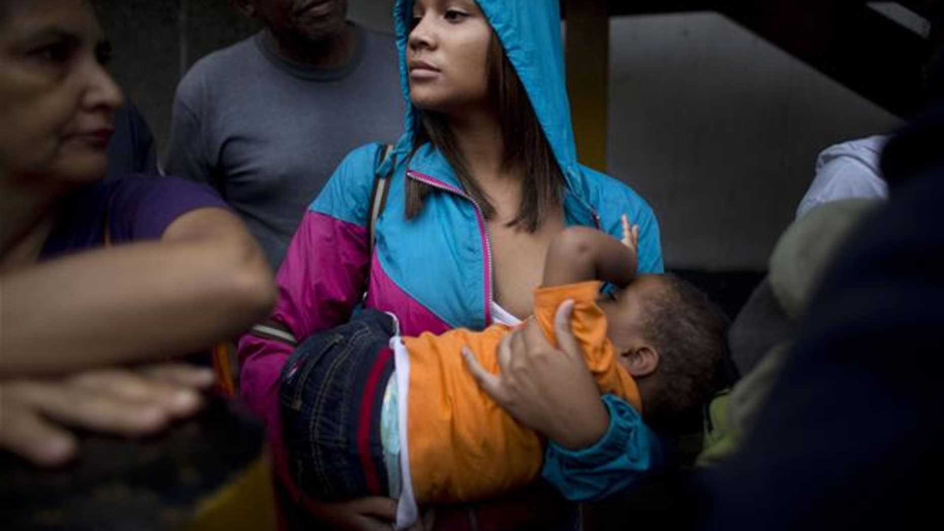 Madeley Vasquez, 16, breast feeds her one-year-old son Joangel as she waits in line outside a supermarket to buy food in Caracas, Venezuela.