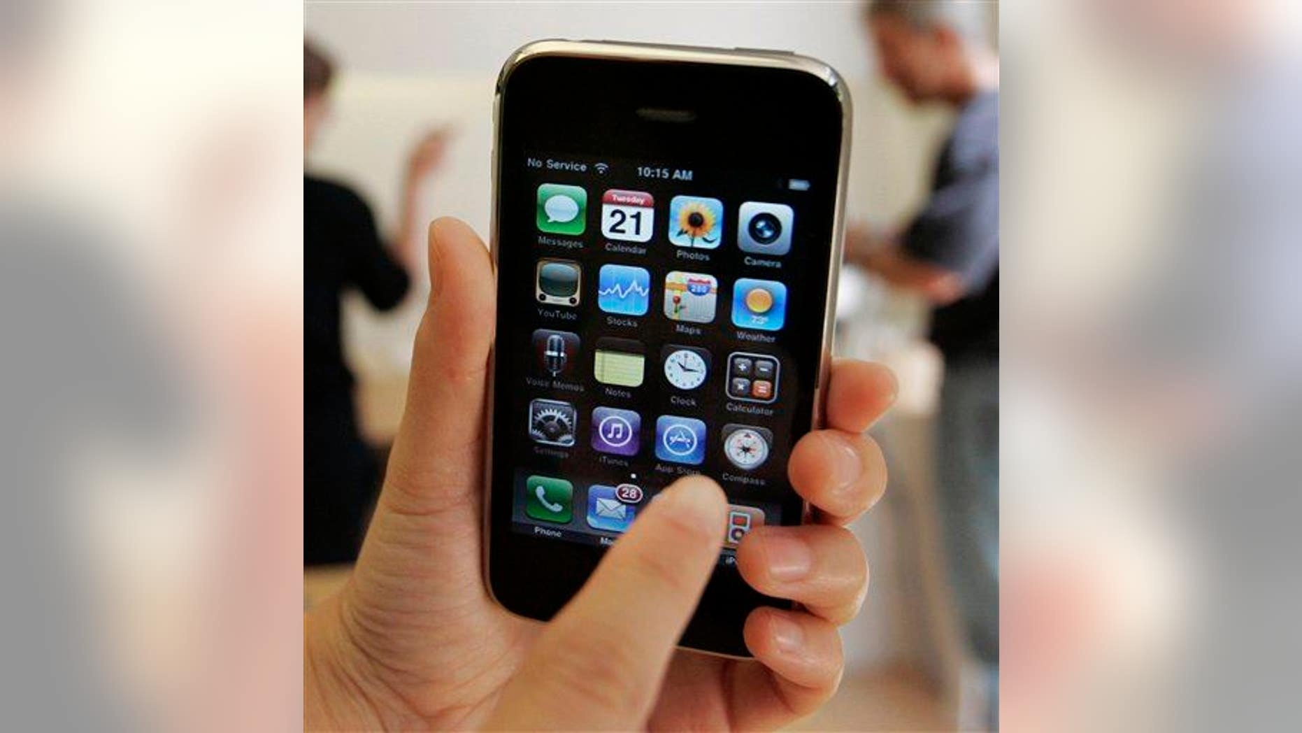 In this July 21, 2009, file photo, a customer displays an Apple iPhone 3GS at an Apple store in Palo Alto, Calif.