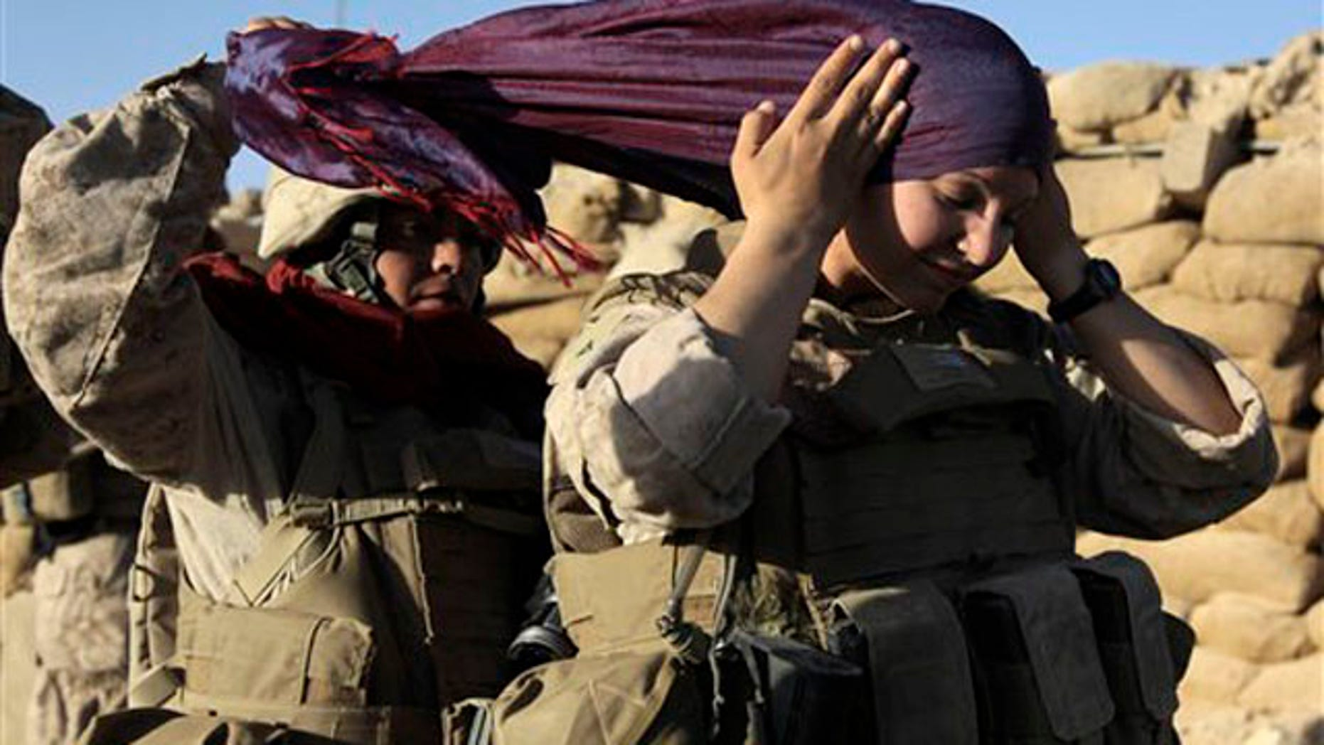FILE - In this photo, U.S. Marine Sgt. Monica Perez, of San Diego, left, helps Lance Cpl. Mary Shloss of Hammond, Ind. put on her head scarf before heading out on a patrol with Golf Company, 2nd Batallion, 3rd Regiment of the 2nd MEB, 2nd MEF, in the village of Khwaja Jamal in the Helmand Province of Afghanistan.