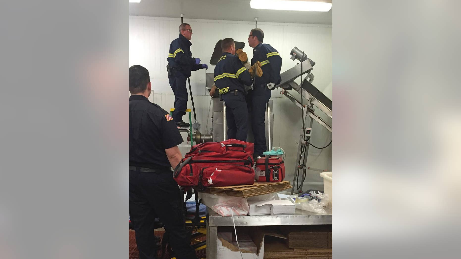 In this July 16, 2015 photo provided by the San Luis Obispo Fire Dept., a worker is assisted by fire personnel after his sleeve was caught in a meat grinder in San Luis Obispo, Calif. Fire officials say the employee at a wholesale California grocer is lucky to be alive after getting caught in a running meat grinder. The worker's sleeve got caught and was being pulled in when a co-worker heard his screams and shut the machine off. Fire crews had to pry the machine open to get the worker out who suffered a broken arm. (Garret Olson/San Luis Obispo Fire Dept. via AP)
