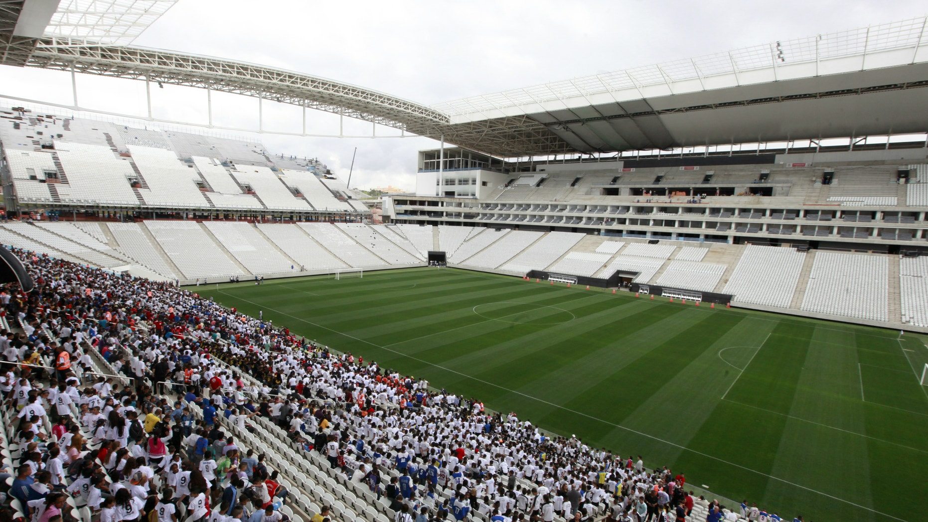 People stand in the bleachers during an infrastructure test at Arena de Sao Paulo Stadium, one of the venues for the 2014 World Cup.