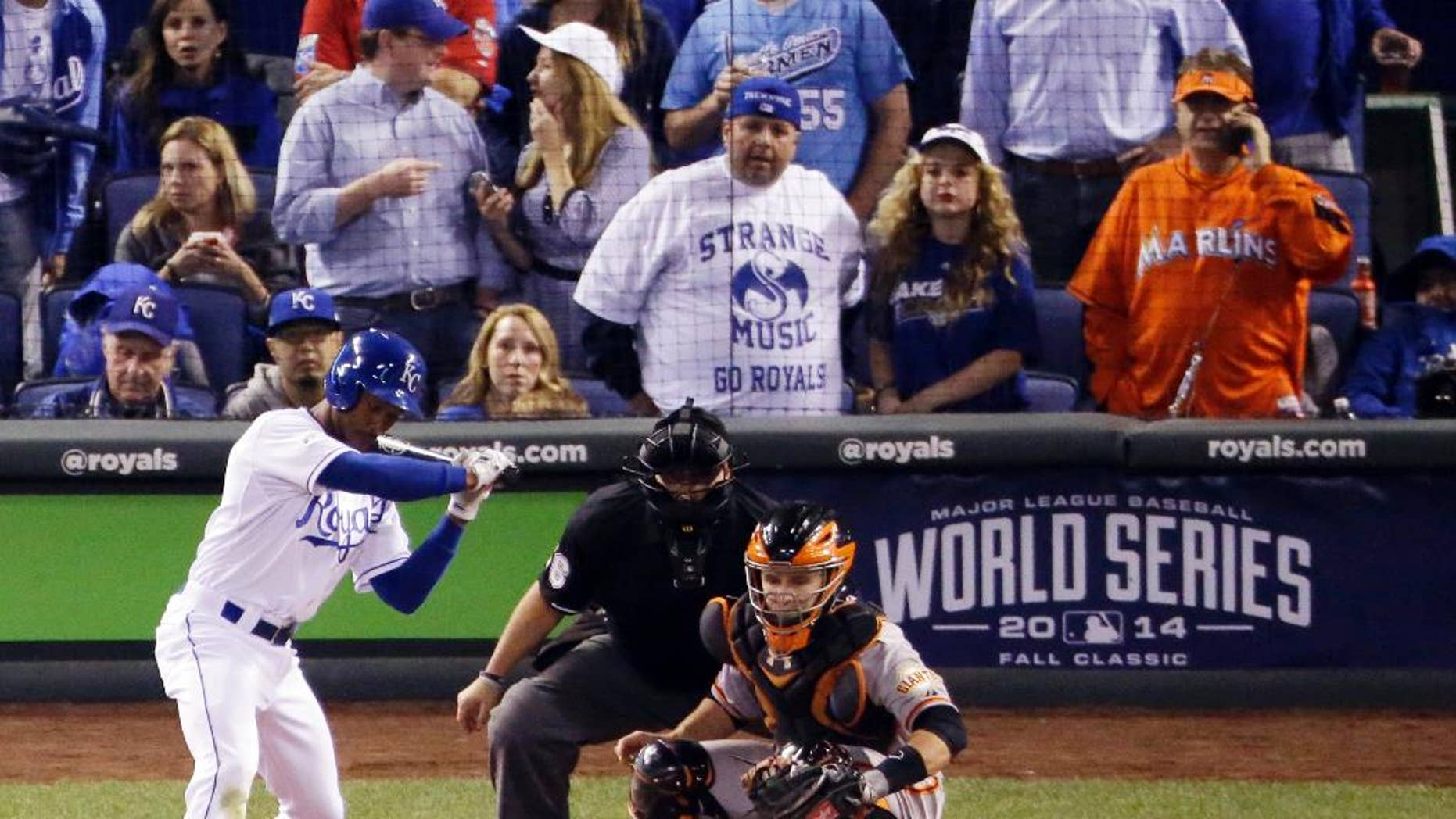 In this Wednesday, Oct. 22, 2014, photo, Miami Marlins fan Laurence Leavy, rear right, is shown wearing a bright orange Marlins jersey during Game 2 of baseball's World Series in Kansas City, Mo. Leavy's orange Marlins jersey made him easy to spot amid a sea of Kansas City Royals blue. He said a Royals official approached him offering to move him to the team owner's suite, but Leavy declined. (AP Photo/Charlie Riedel)