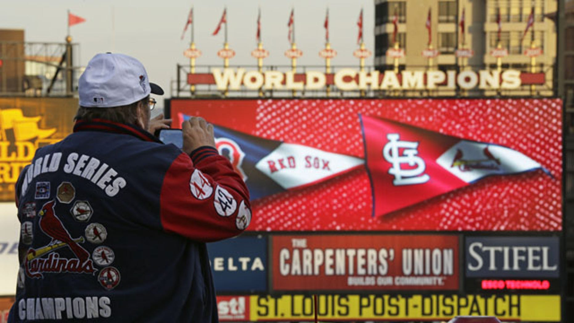 October 28, 2013: John Koenig takes a photo as players warm up for Game 5 of baseball's World Series between the Boston Red Sox and the St. Louis Cardinals in St. Louis. (AP Photo/Charlie Riedel)