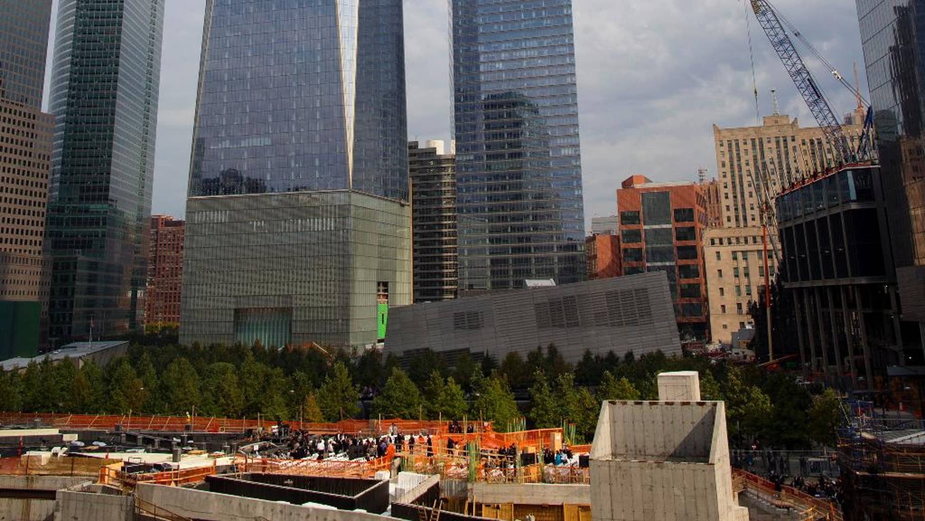 File-This Oct. 18, 2014, file photo shows One World Trade Center in the background, as people gather, bottom, for a groundbreaking ceremony at the site of the St. Nicholas National Shrine, in New York.  Thirteen years after the 9/11 terrorist attack, the resurrected World Trade Center is again opening for business, marking an emotional milestone for both New Yorkers and the nation. Publishing giant Conde Nast will start moving Monday, Nov. 3, 2014, into One World Trade, a 104-story, $3.9 billion skyscraper that dominates the Manhattan skyline. It is America's tallest building. (AP Photo/Craig Ruttle, File)