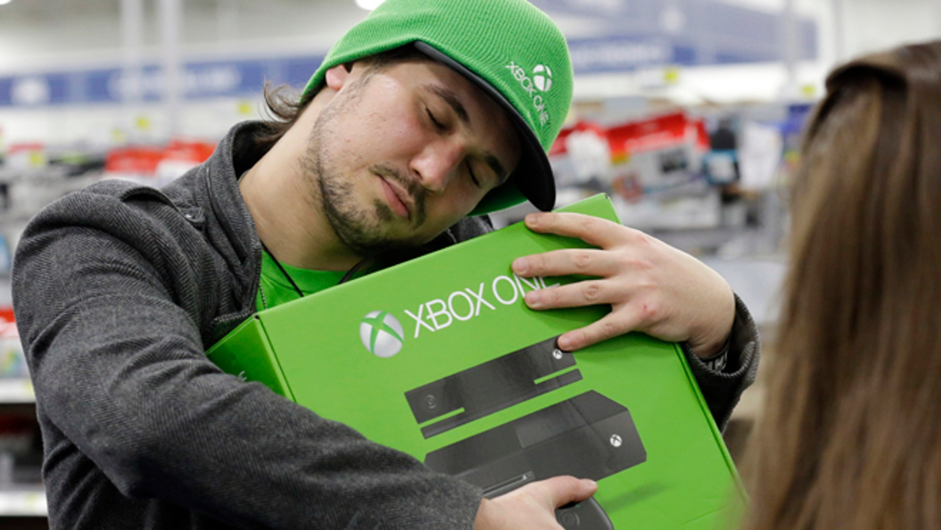 Emanuel Jumatate, from Chicago, hugs his new Xbox One after he purchased it at a Best Buy on Friday, Nov. 22, 2013, in Evanston, Ill. Microsoft is billing the Xbox One, which includes an updated Kinect motion sensor, as an all-in-one entertainment system rather than just a gaming console. (AP Photo/Nam Y. Huh)