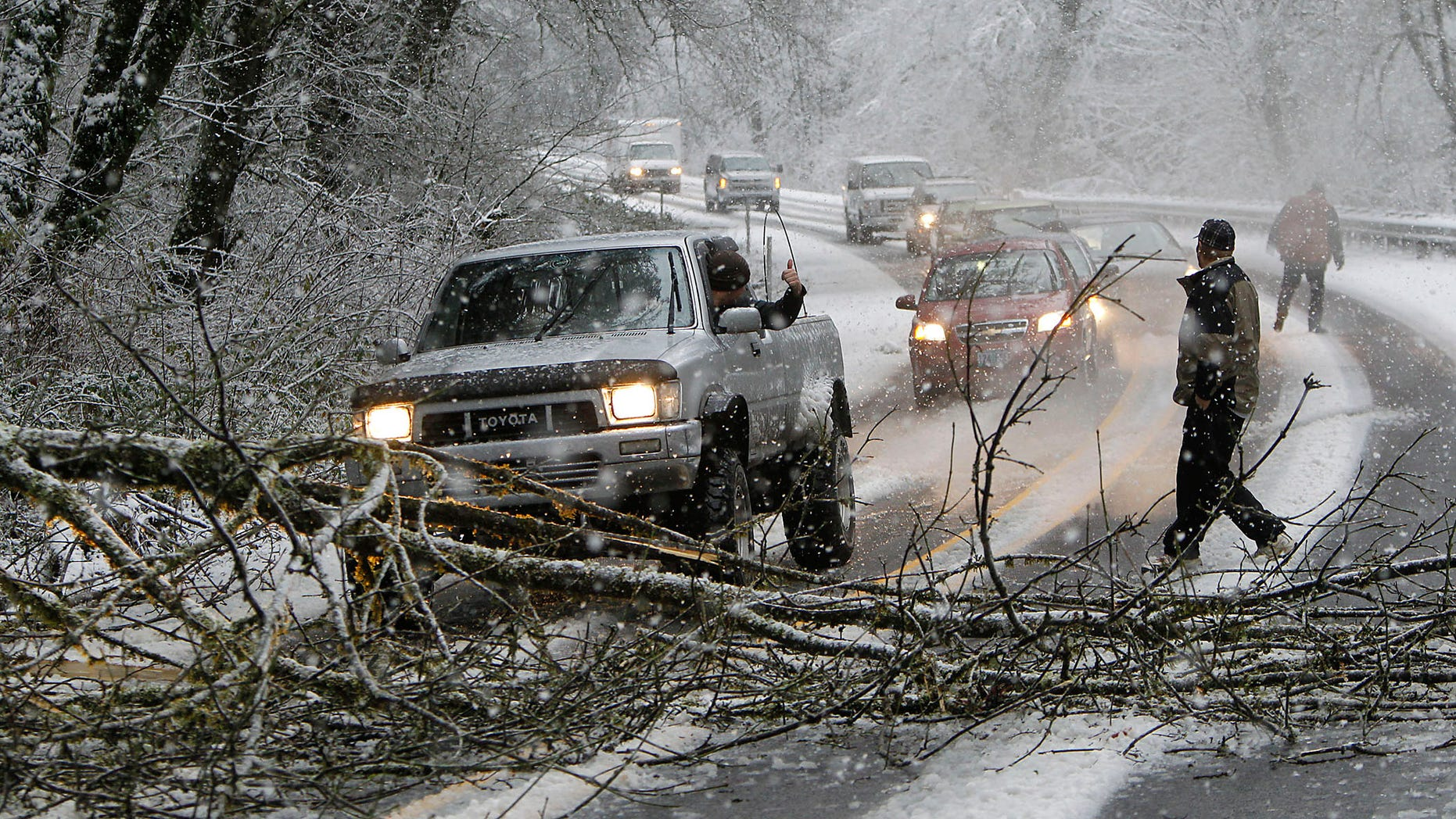 Dec. 20, 2012: A motorist in a pickup truck pulls a tree out of the way about five miles East of Mapleton, Ore. as heavy snow in the Oregon Coast Range caused trees to fall across Highway 126 Thursday morning.