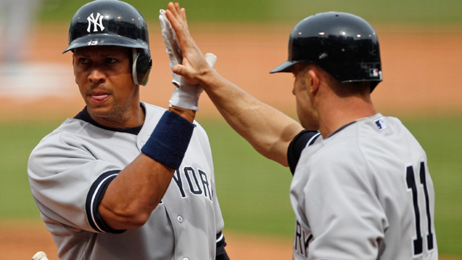 April 8, 2011: New York Yankees Alex Rodriguez, left, celebrates with teammate Brett Gardner after being driven home on a double by Robinson Cano during the first inning of a baseball game at Fenway Park in Boston.