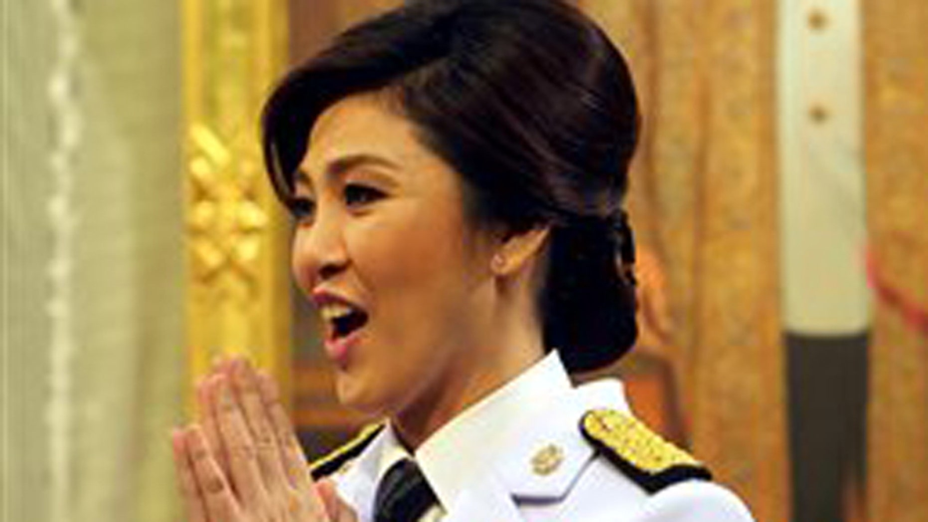 Thai Prime Minister Yingluck Shinawatra greets after receiving the royal command appointed her as the country's prime minister in front of a portrait of King Bhumibol Adulyadej at her Pheu Thai party headquarters in Bangkok, Thailand, Monday, Aug. 8 2011. Yingluck, 44, U.S.-educated businesswoman, became the country's first female prime minister. (AP Photo/Rungroj Yongrit, Pool)