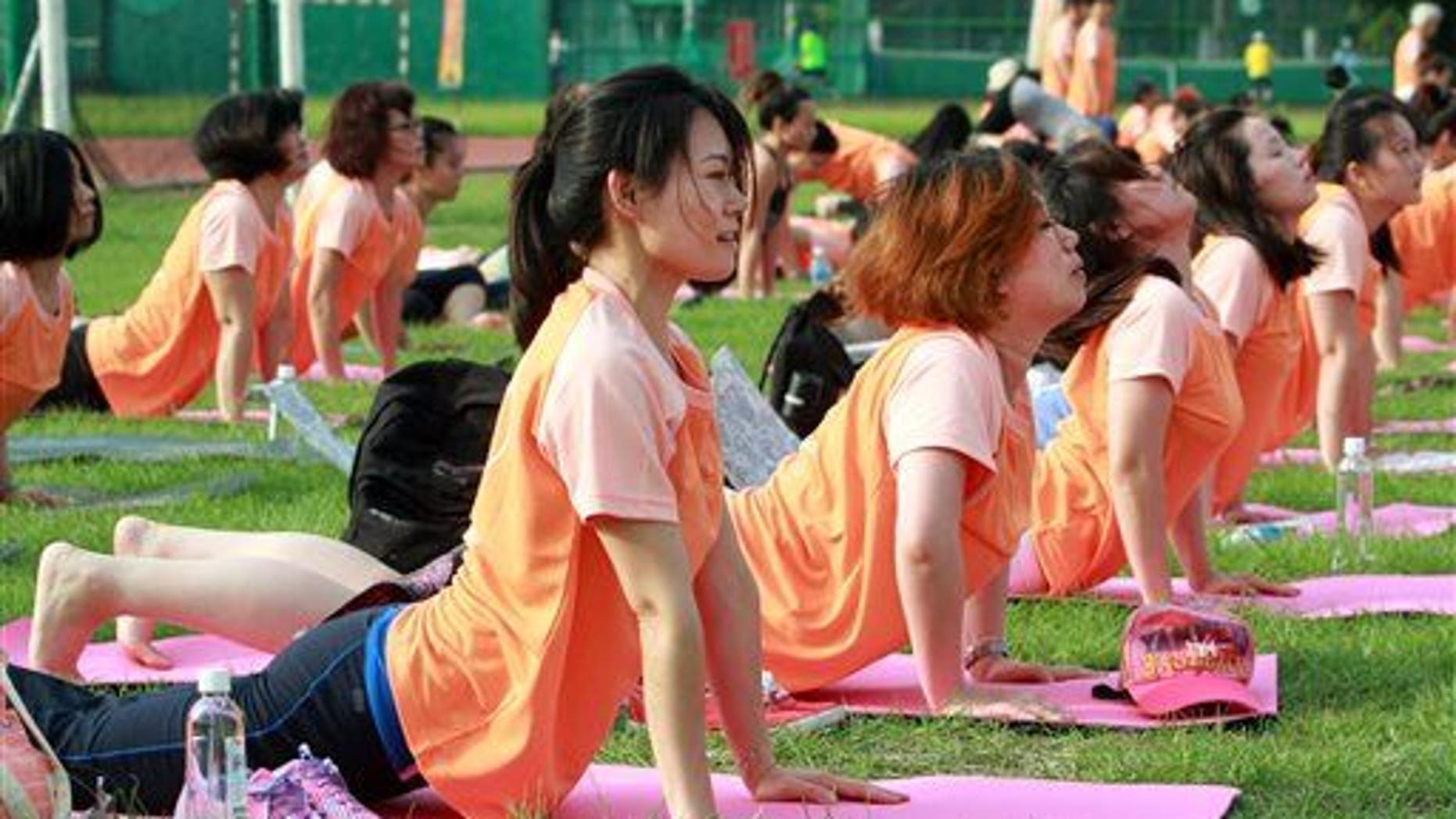 Taiwanese perform yoga poses at the start of International Yoga Day in Taipei, Taiwan, June 21, 2015.