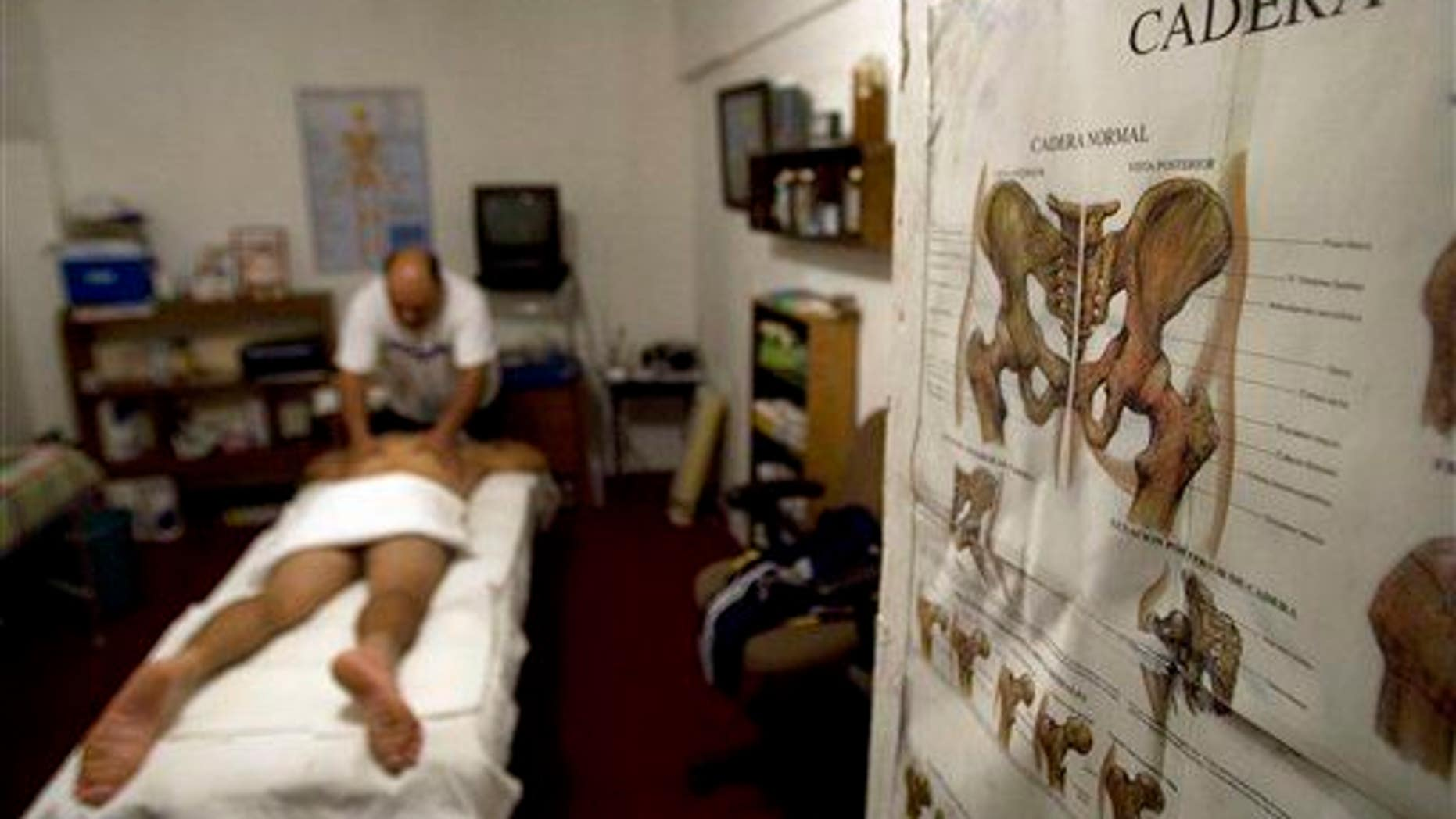 "Juventino Luna Moreno, a masseur or ""sobador,"" works on a patient in Tijuana, Mexico, on Jan. 10, 2009. Sobadores are chiropractors with no formal training, who use a mix of massage and faith."