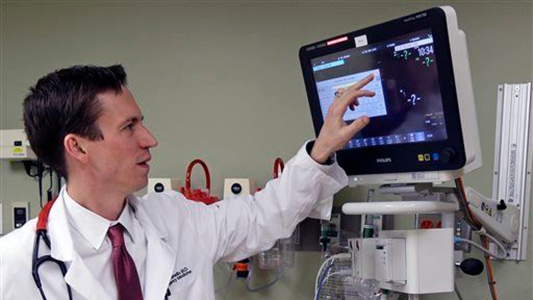 In this Feb. 11, 2014, photo, Dr. Marcus Romanello, checks equipment in the emergency room of Fort Hamilton Hospital in Hamilton, Ohio.