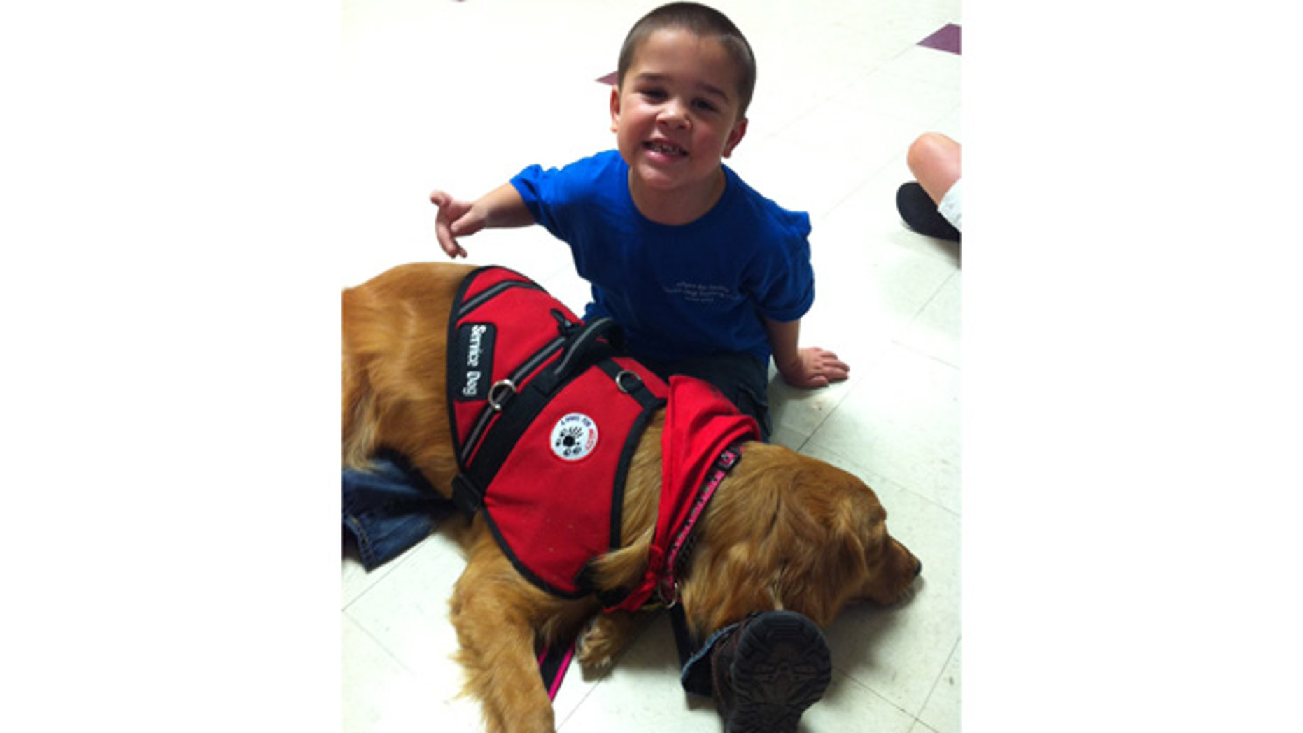 "Seven-year-old Zachary Sorrells, of Ward, Ark., is seen here with his service dog named, ""Majesty."""