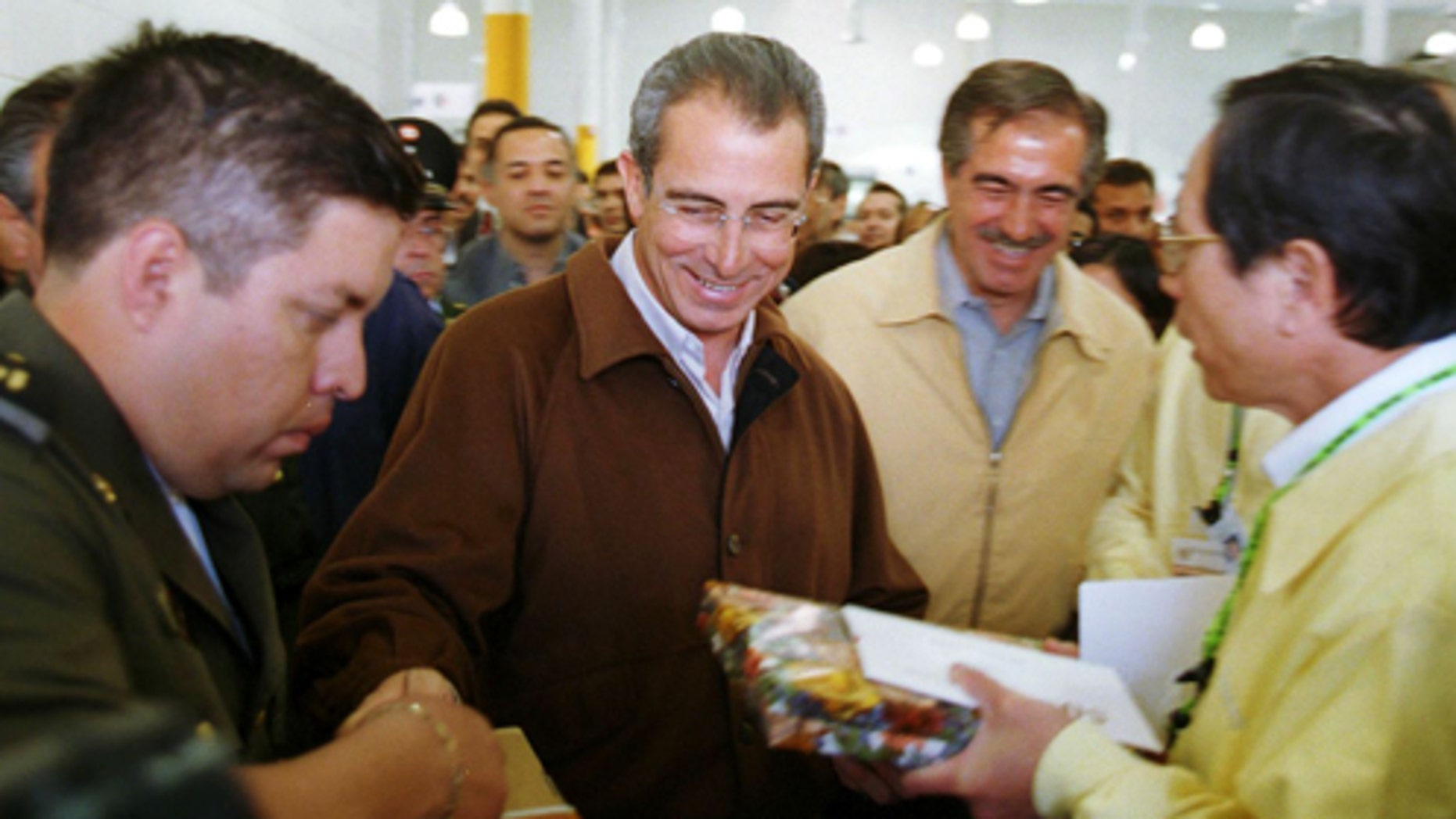 Mexico's president Ernesto Zedillo (in brown jacket) and Chihuahua state governor, Patricio Martinez, (to right) are given gifts as they leave the new Acer maquiladora in Ciudad Juarez, Mexico February 23, 2000. (Photo by Joe Raedle)