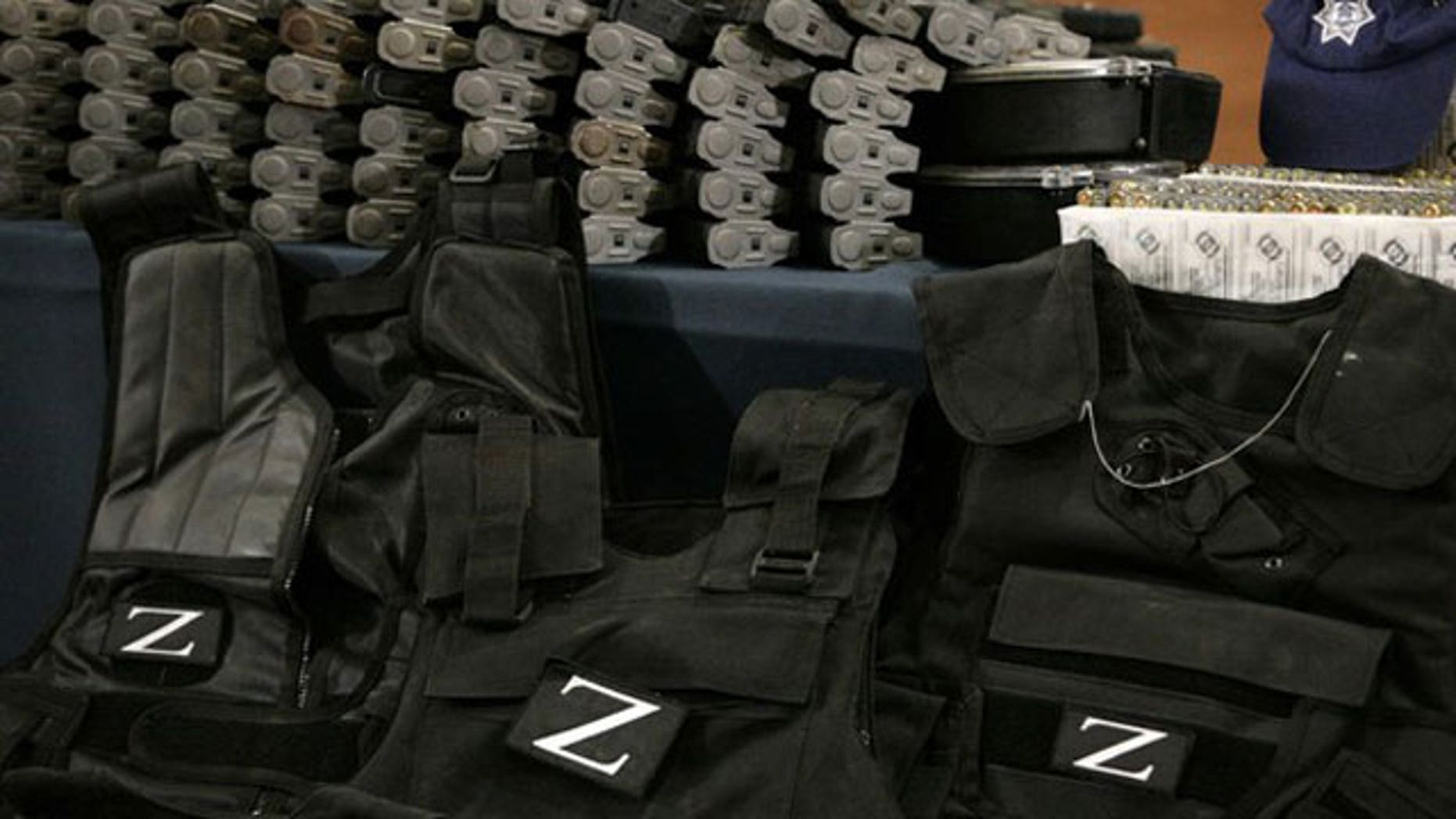 """December 13, 2011: Flak jackets with the Zetas drug cartel's """"Z"""" logo, cartridges and boxes with bullets are on display during a presentation to the media in Mexico City."""