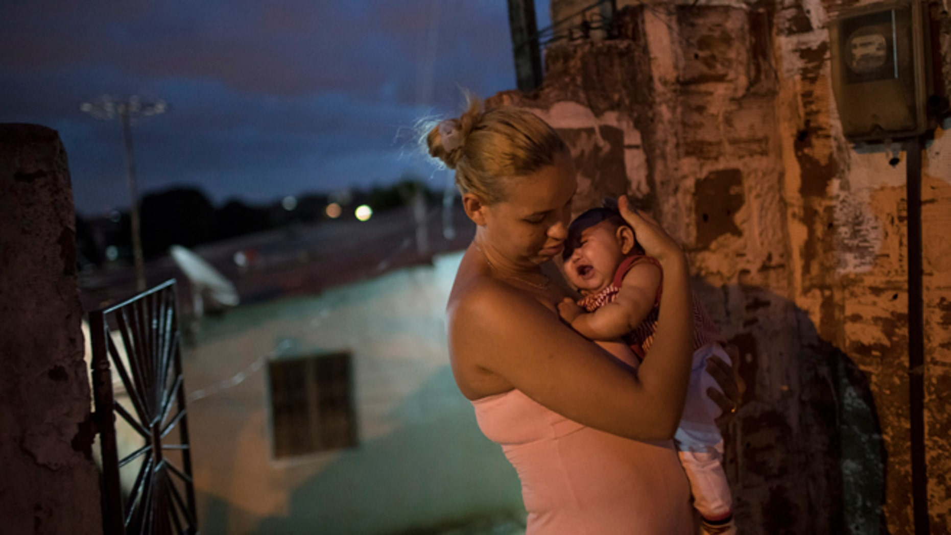 FILE - In this Wednesday, Jan. 27, 2016 file photo, Gleyse Kelly da Silva, 27, holds her daughter Maria Giovanna, who was born with microcephaly, outside their house in Recife, Pernambuco state, Brazil. Women who got pregnant during a Zika outbreak in Tahiti two years ago had about a 1 percent chance of having a baby with an abnormally small head, according to a new study published Tuesday, March 15. It's a surprisingly low risk that experts say might not match the threat of the epidemic now spreading explosively in the Americas.  The World Health Organization declared Zika to be a global emergency last month, based on suspicions it is causing a spike in a worrying birth defect known as microcephaly as well as a rare condition that sometimes results in temporary paralysis.  (AP Photo/Felipe Dana, file)