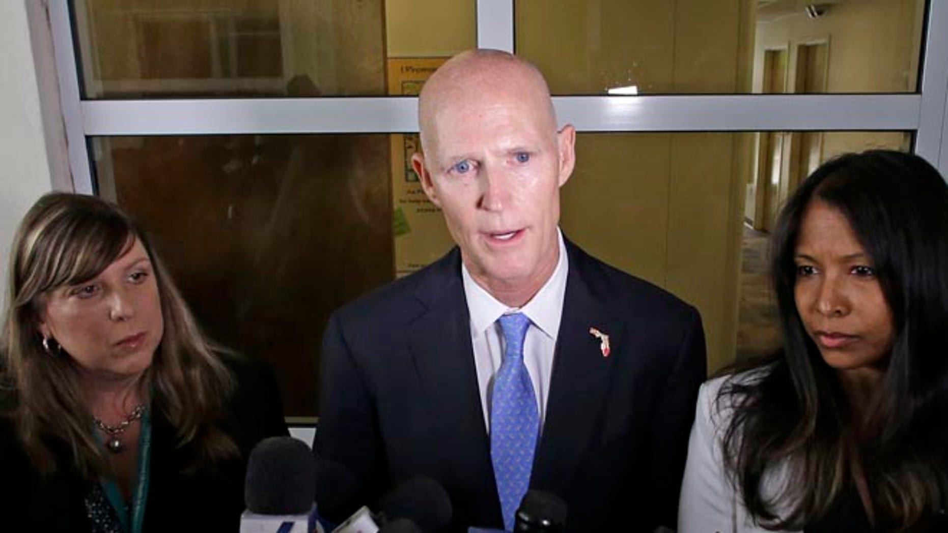 Gov. Rick Scott flanked by Dr. Paula Thaqi, Director of the Broward County Health Department, left, and Dr. Celeste Philip, State Surgeon General.
