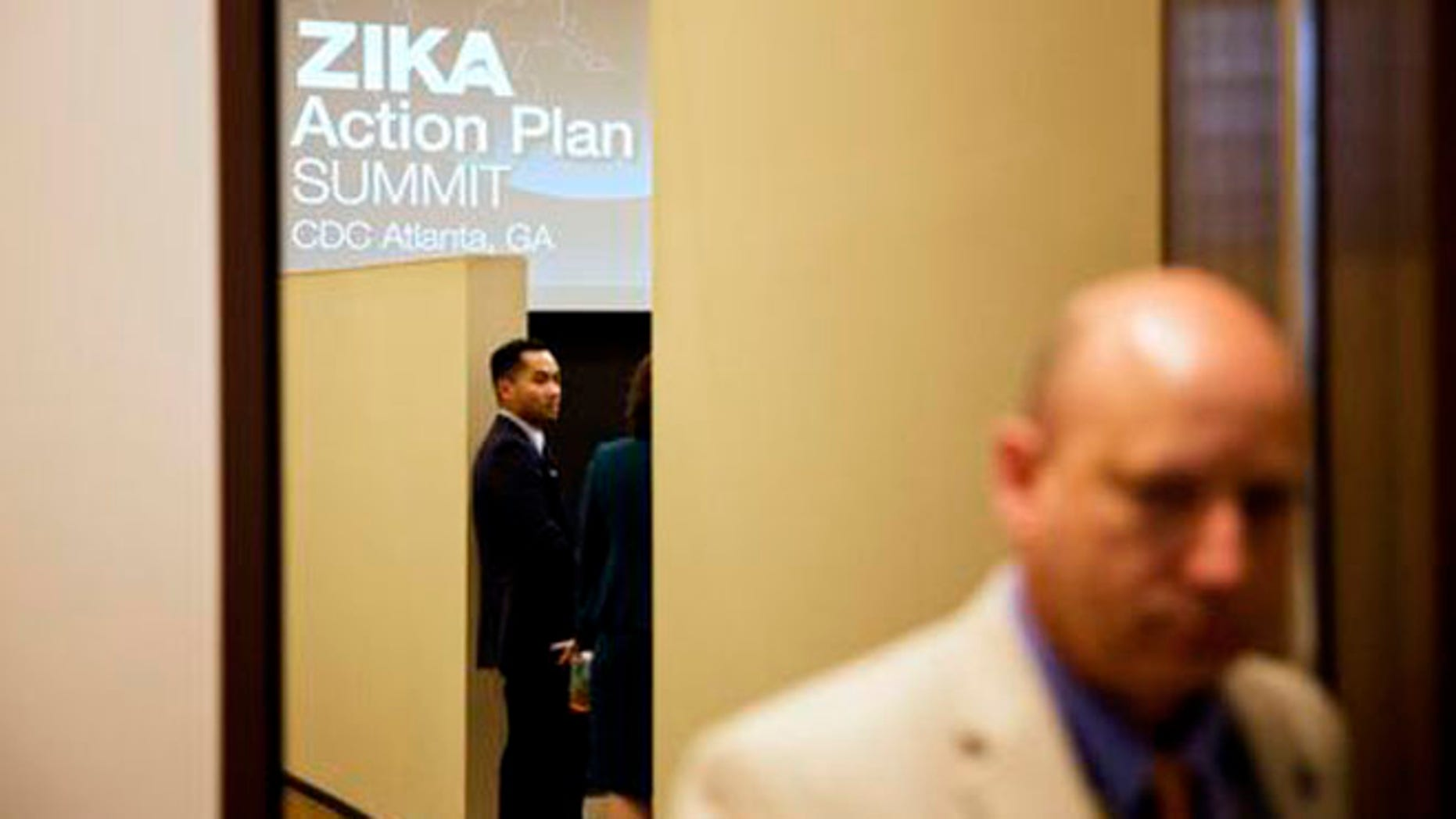 A graphic is displayed on a screen as attendees wait for a seminar to begin at a one-day Zika summit at the Centers for Disease Control and Prevention Friday, April 1, 2016, in Atlanta. The government is urging health officials from around the country to prepare for potential outbreaks of the mosquito-borne virus in the U.S. (AP Photo/David Goldman)