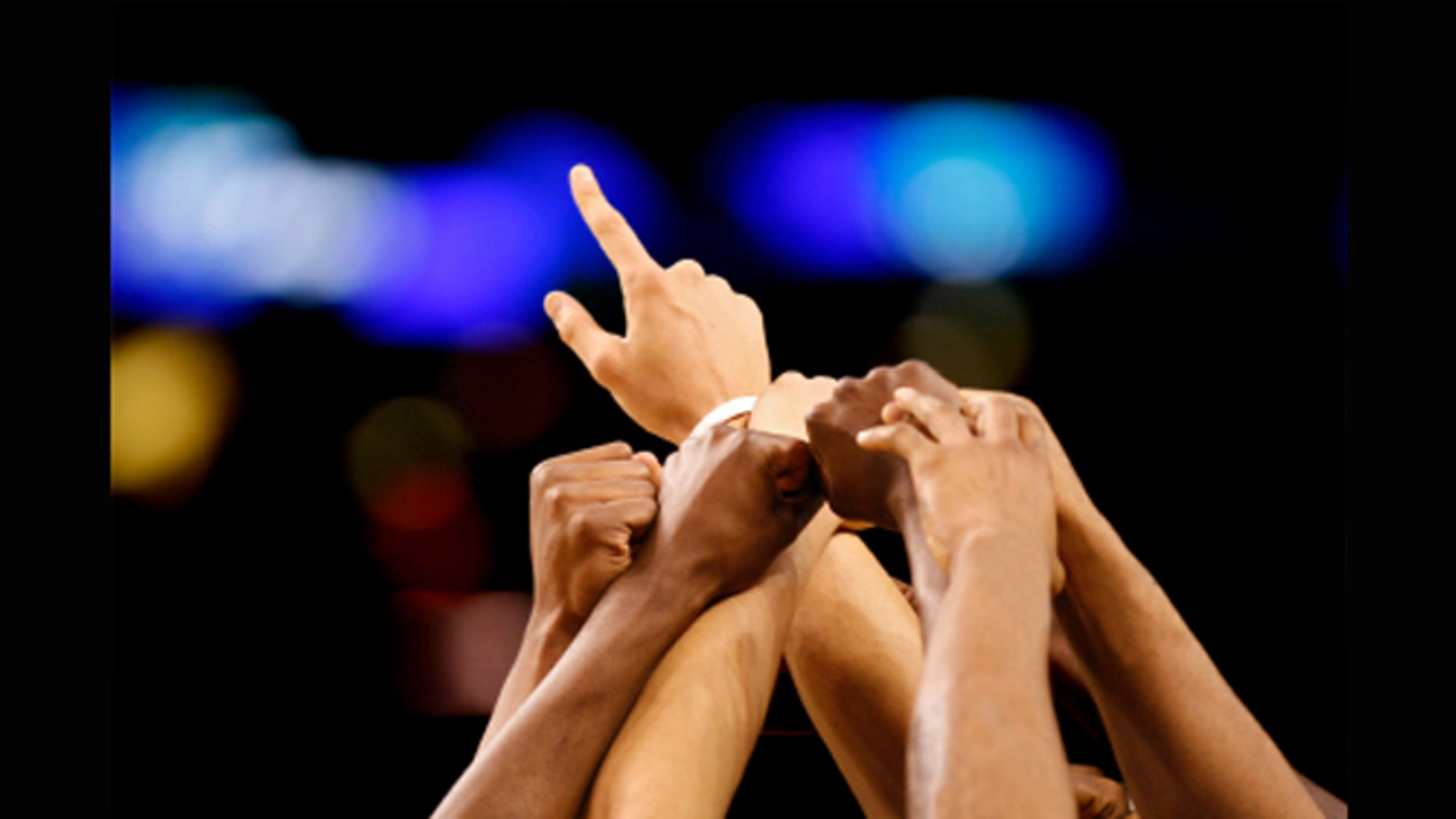 A collection of hands reach toward a central goal before a sporting event.