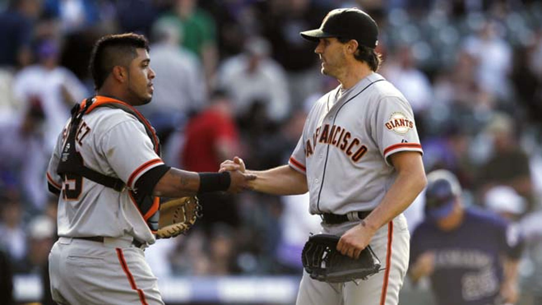 San Francisco Giants catcher Hector Sanchez, left, congratulates starting pitcher Barry Zito after he notched the final out in the ninth inning for a shut out in the Giants' 7-0 victory over the Colorado Rockies in a baseball game in Denver on Monday, April 9, 2012.