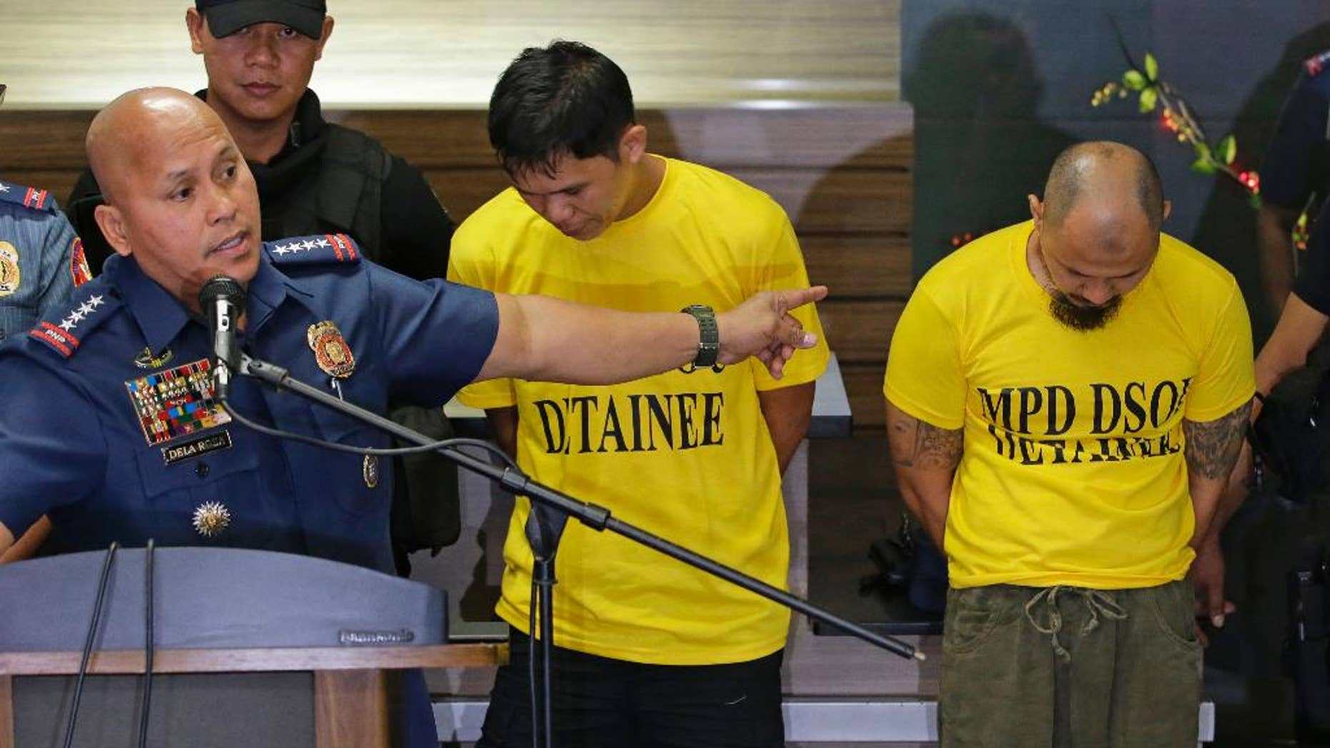 Suspects Jiaher Guinar, center, and Rashid Kilala, right, presented to reporters at police headquarters in Quezon city, north of Manila, Philippines.