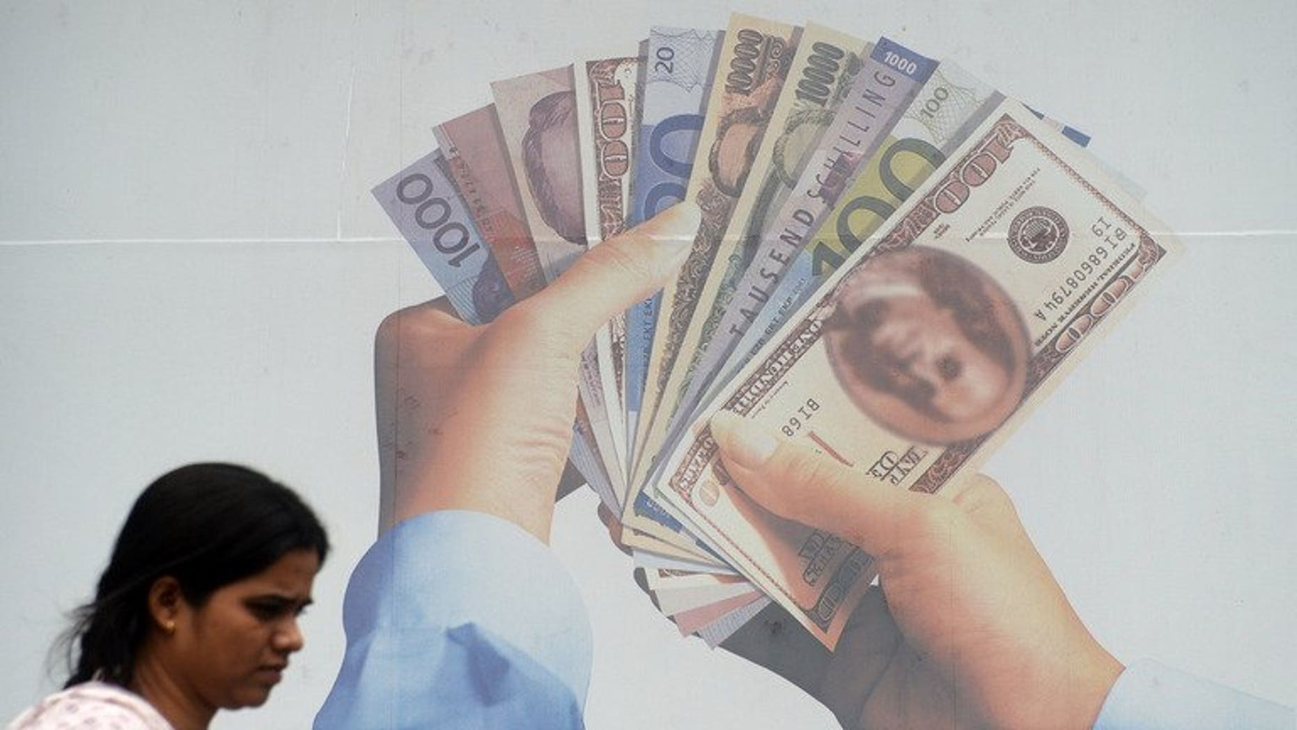 A pedestrian walks past a foreign exchange advertising billboard in Mumbai, on June 20, 2013. Rupee firmed against the dollar on Friday, a day after a government advisor said steps were being taken to boost growth and reduce the high current account deficit.