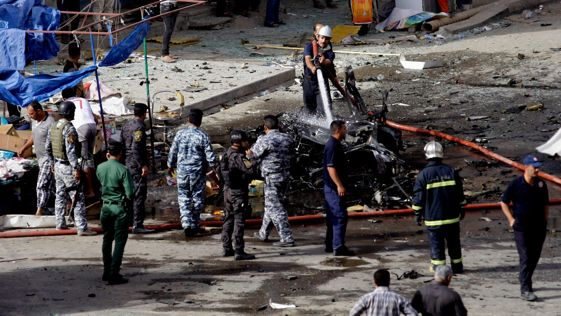Security forces inspect the scene of a car bomb attack in the Baghdad, Iraq, Monday, May 27, 2013. A parked car bomb explosion in the busy commercial Sadoun Street in central Baghdad, killed and wounded scores of people, police said. (AP Photo/Khalid Mohammed)