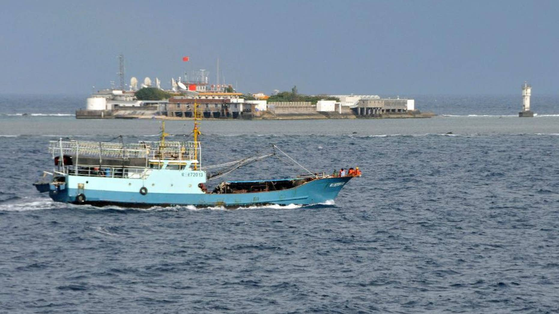 FILE - In this July 15, 2012 file photo released by China's Xinhua News Agency, a Chinese fishing vessel sails by Fiery Cross Reef, background, also known as Yongshu Reef by the Chinese, of the Spratly Islands in South China Sea. Defying a U.S. call to halt the project, China defended its land reclamation in the disputed Spratly Islands on Monday, Nov. 24, 2014, saying the work is for public service use, although a London-based security group says the new island could host a military airfield to intimidate neighbors. In a recent report, IHS Jane's said satellite images taken in August and November showed that Chinese dredgers had created a land mass almost the entire length of Fiery Cross Reef, which was previously under water. The security group said it is China's largest construction project in the island chain. (AP Photo/Xinhua, Wang Cunfu, File) NO SALES