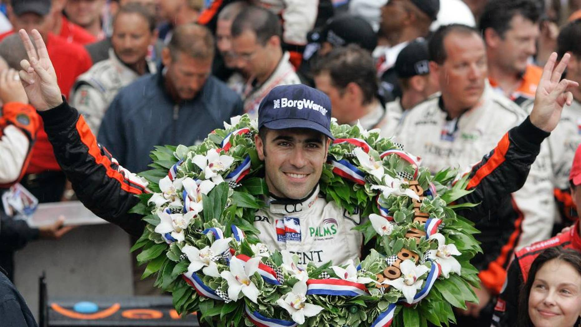 FILE - In this May 27, 2007, file photo, Dario Franchitti, of Scotland, gestures after his win in the Indianapolis 500 auto race at Indianapolis Motor Speedway in Indianapolis, Ind. At lower right is his wife, actress Ashley Judd. (AP Photo/Darron Cummings, File)