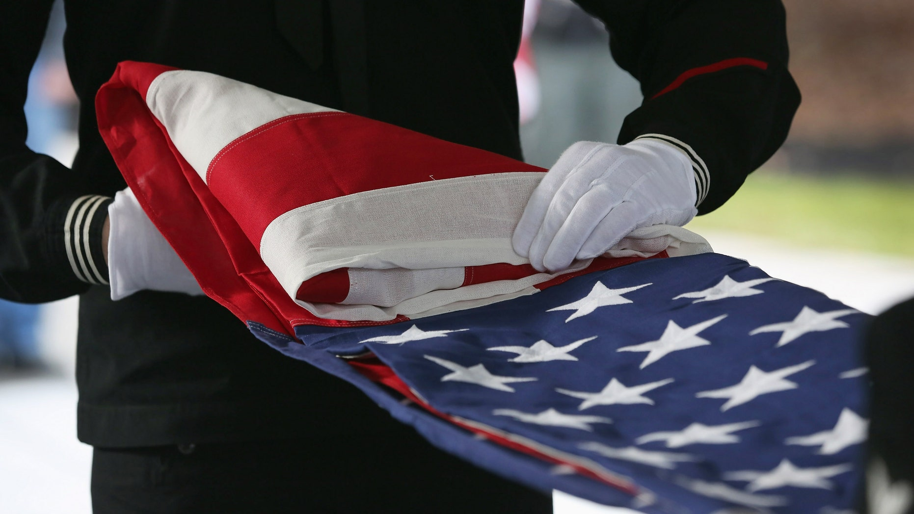WADING RIVER, NY - DECEMBER 11:  A U.S. Navy honor guard folds an American flag after removing it from the casket of Hurricane Sandy victim David Maxwell, before his burial at the Calverton National Cemetery on December 11, 2012 near the Wading River hamlet of Long Island, New York. Maxwell, 66, was the last of Sandy's victims found on the Staten Island borough of New York City, when his body was discovered in his Midland Beach home 11 days after the storm. A Vietnam veteran, he was buried at the national cemetery, accompanied by honor guards from the Catholic War Veterans and the Patriot Guard Riders.  (Photo by John Moore/Getty Images)