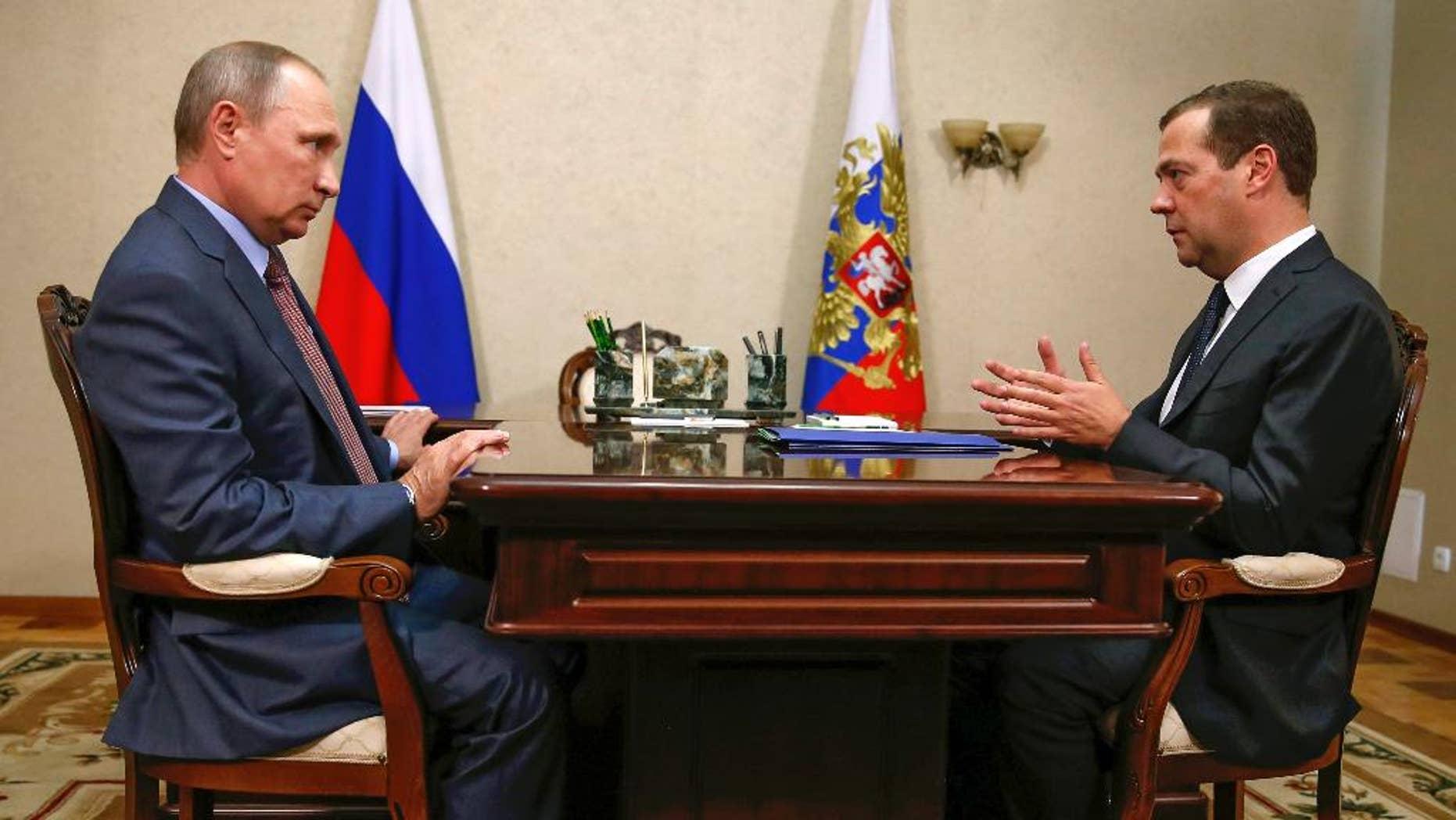 Russian President Vladimir Putin, left, and Prime Minister Dmitry Medvedev meet in Belbek in Crimea, Friday, Aug. 19, 2016. (Dmitry Astakhov/Sputnik, Government Pool Photo via AP)