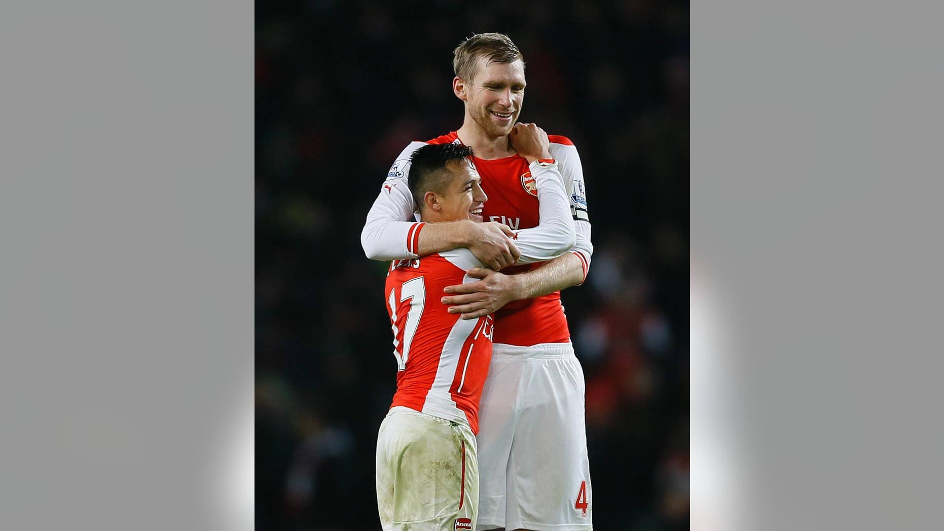 Arsenal's captain Per Mertesacker, right, celebrates with goal scorer Alexis Sanchez  at the end the English Premier League soccer match between Arsenal and Southampton at Emirates stadium in London, Wednesday, Dec. 3, 2014. (AP Photo/Kirsty Wigglesworth)
