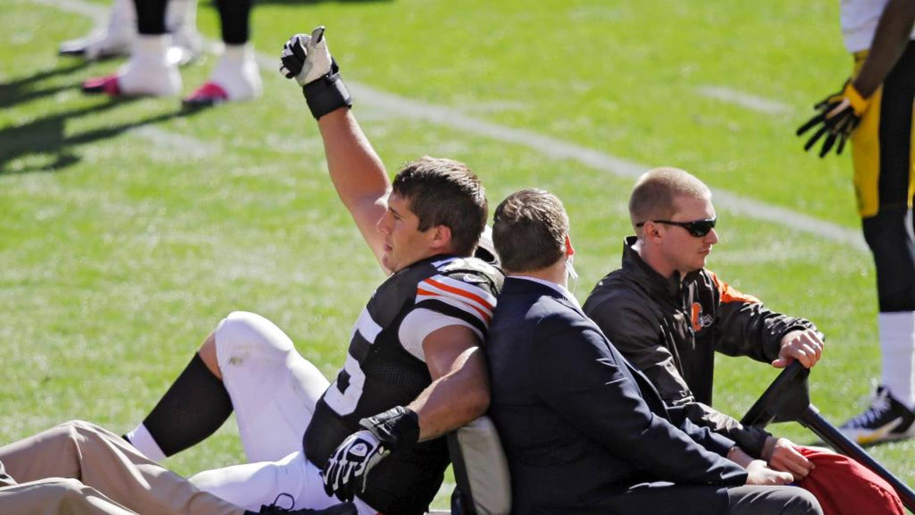 Cleveland Browns center Alex Mack gives a thumbs-upto the crowd as he is taken off the field with an injury in the second quarter of an NFL football game against the Pittsburgh Steelers, Sunday, Oct. 12, 2014, in Cleveland. The Browns won 31-10. (AP Photo/Tony Dejak)