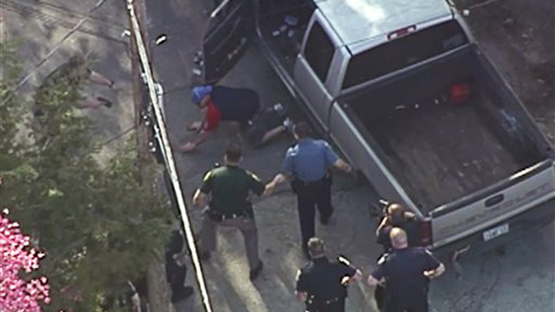 This aerial image made from a helicopter video provided by WHDH shows Richard Simone kneeling and putting his hands on the ground after a high-speed police pursuit in Nashua, N.H., Wednesday, May 11, 2016.