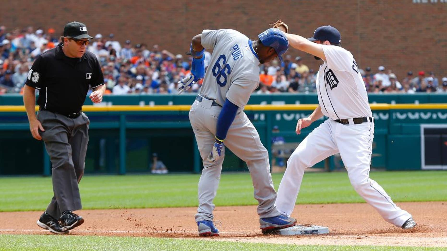 Detroit Tigers third baseman Nick Castellanos shows the ball to third base umpire Paul Schrieber after tagging third base before Los Angeles Dodgers' Yasiel Puig (66) could tag up on a Hanley Ramirez fielders choice in the first inning of a baseball game in Detroit, Wednesday, July 9, 2014. Puig was out on the play. (AP Photo/Paul Sancya)