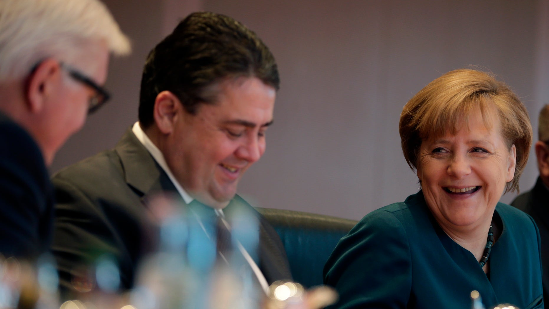 German Chancellor Angela Merkel, German Economy and Energy Minister Sigmar Gabriel and German Foreign Minister Frank-Walter Steinmeier, from right, chat at the beginning of the weekly cabinet meeting at the chancellery in Berlin, Germany, Wednesday, Jan. 15, 2014. (AP Photo/Michael Sohn)