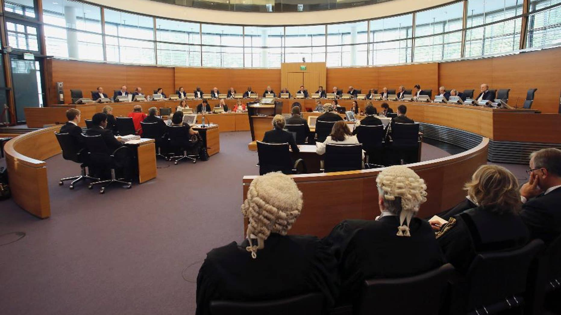"""FILE - In this Aug. 10, 2015 file picture the UN mandated tribunal and the delegations of India, left, and Italy, right, are pictured during the first public hearing on the request for provisional measures in the """"Enrica Lexie"""" incident at the International Tribunal for the Law of the Sea in Hamburg, northern Germany.  The tribunal has ordered India to put on hold legal proceedings against two Italian marines accused of killing two Indian fishermen in 2012. The tribunal on Monday Aug. 24, 2015  ordered both sides to suspend """"all court proceedings"""" and refrain from initiating new ones pending an arbitration decision. (AP Photo/Focke Strangmann,file)"""