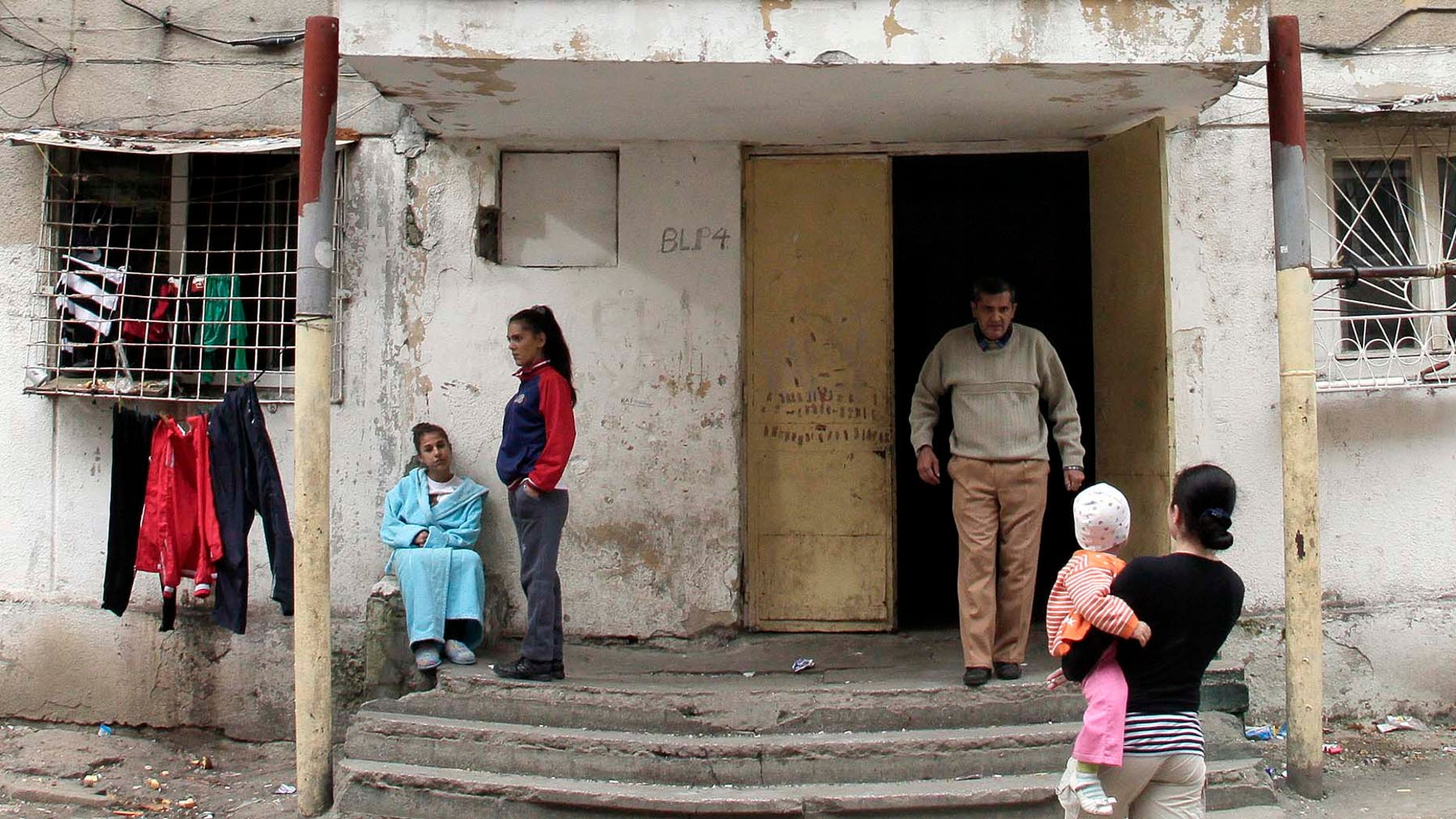 """Romanian Gypsy residents are seen outside the apartment block that was home to Romanian girl that gave birth in Spain last week in Bucharest, Romania, Tuesday, Nov. 9, 2010. The former neighbors of a Romanian girl who gave birth last week in Spain on Tuesday claimed that she is more than 10 years old. Neighbors gathered outside the shabby four-story apartment building where the girl spent her early years before moving to Spain. They told the Associated Press they were indignant about """"lies"""" that the girl was just 10 when she became a mother. Several neighbors in Bucharest's impoverished Ferentari district said they believed she was between 13 and 15 years old.(AP Photo/Vadim Ghirda)"""