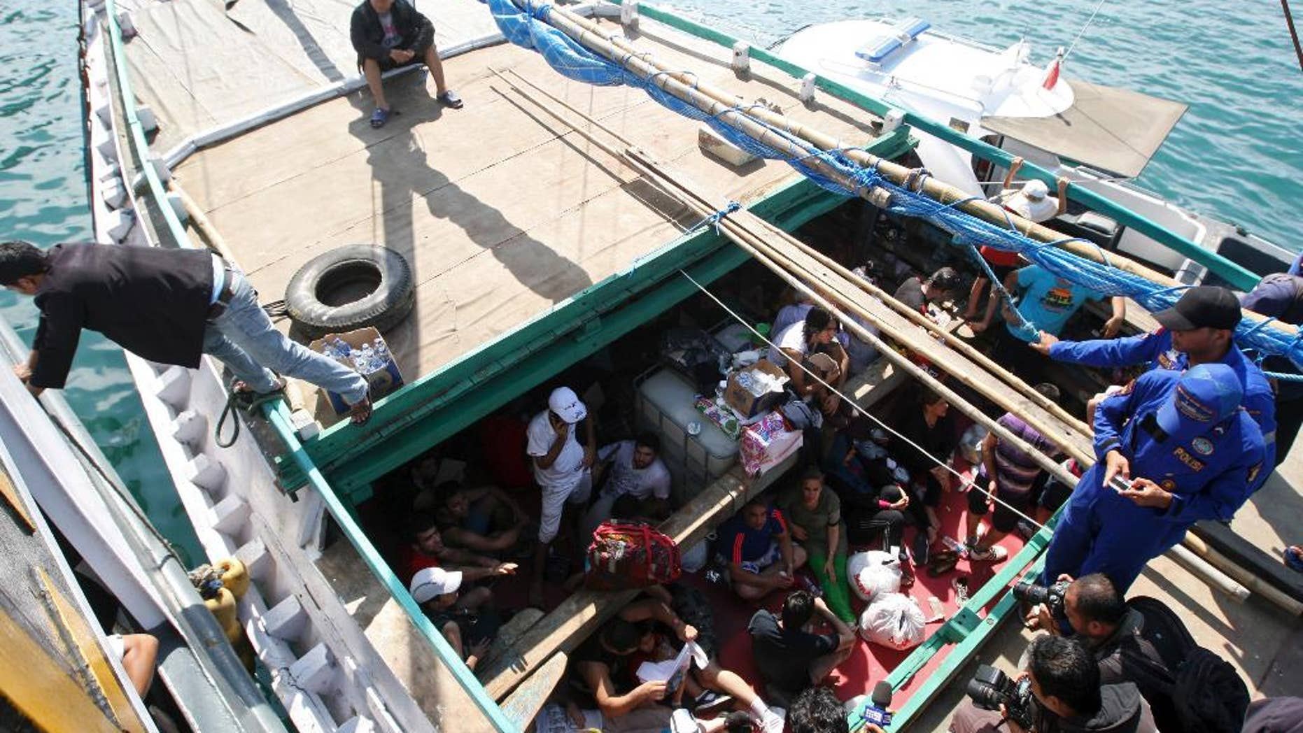 FILE - In this May 12, 2013 file photo, Iranian asylum seekers who were caught in Indonesian waters while sailing to Australia sit on a boat at Benoa port in Bali, Indonesia. Papua New Guinea's Supreme Court on Tuesday, April 26, 2016 ruled that Australia's detention of asylum seekers at a facility on the country's Manus Island is unconstitutional. The Pacific island nation's ruling could jeopardize Australia's divisive policy of refusing to accept any asylum seekers who attempt to reach its shores by boat. The country pays Papua New Guinea and the tiny Pacific island nation of Nauru to hold them in detention camps instead. (AP Photo/Firdia Lisnawati, File)