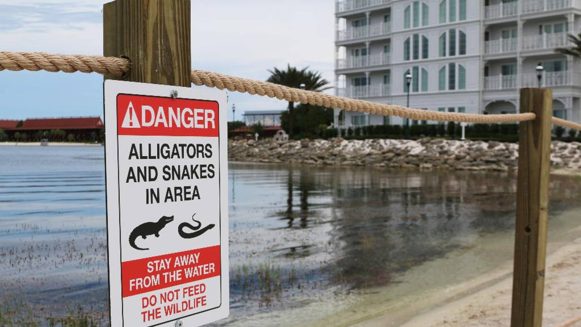 In this Friday, June, 17, 2016 photo released by Walt Disney World Resort, a new sign is seen posted on a beach outside a hotel at a Walt Disney World resort in Lake Buena Vista, Fla. Private family services have been scheduled  for a 2-year-old Nebraska boy killed by an alligator at Disney World. Authorities say an alligator pulled Lane Graves into the water last Tuesday, June 14, 2016, despite the frantic efforts of his father. Lane's body was recovered Wednesday. (Walt Disney World Resort via AP)