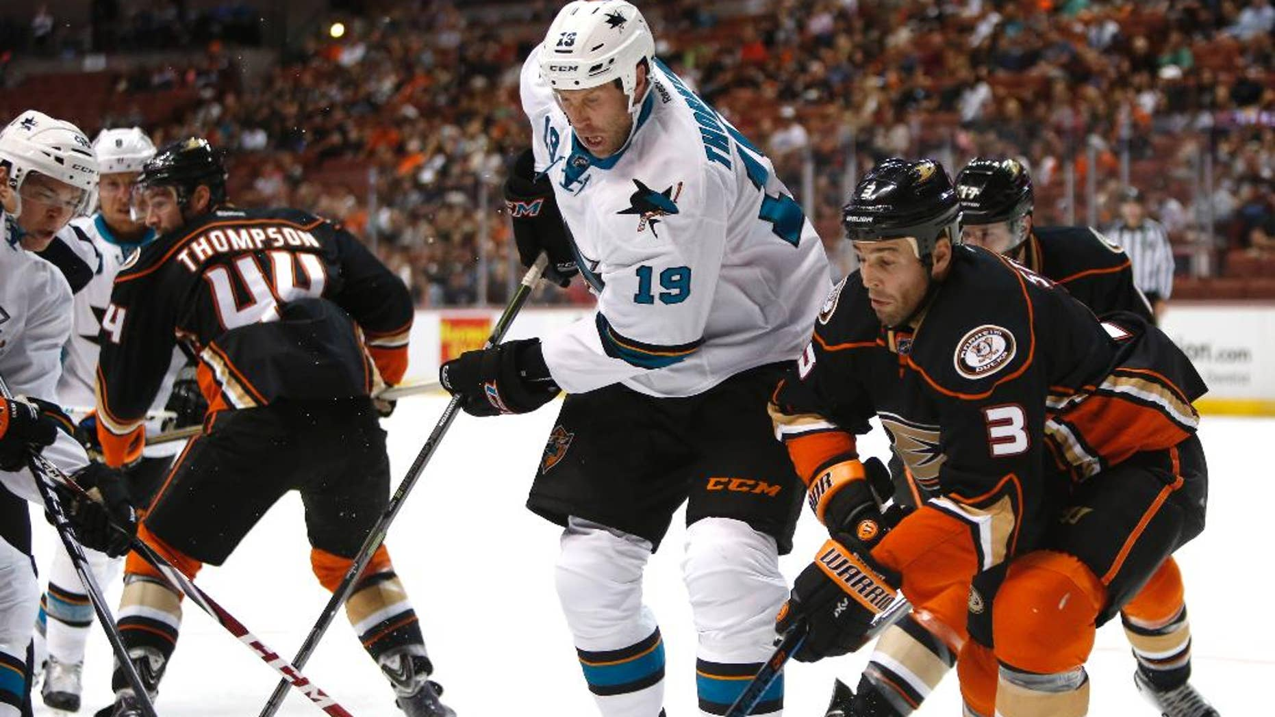 San Jose Sharks center Joe Thornton (19) works for the puck against Anaheim Ducks defenseman Clayton Stoner (3) during the first period of a preseason NHL hockey game in Anaheim, Calif., on Saturday, Oct. 4, 2014. (AP Photo/Christine Cotter)