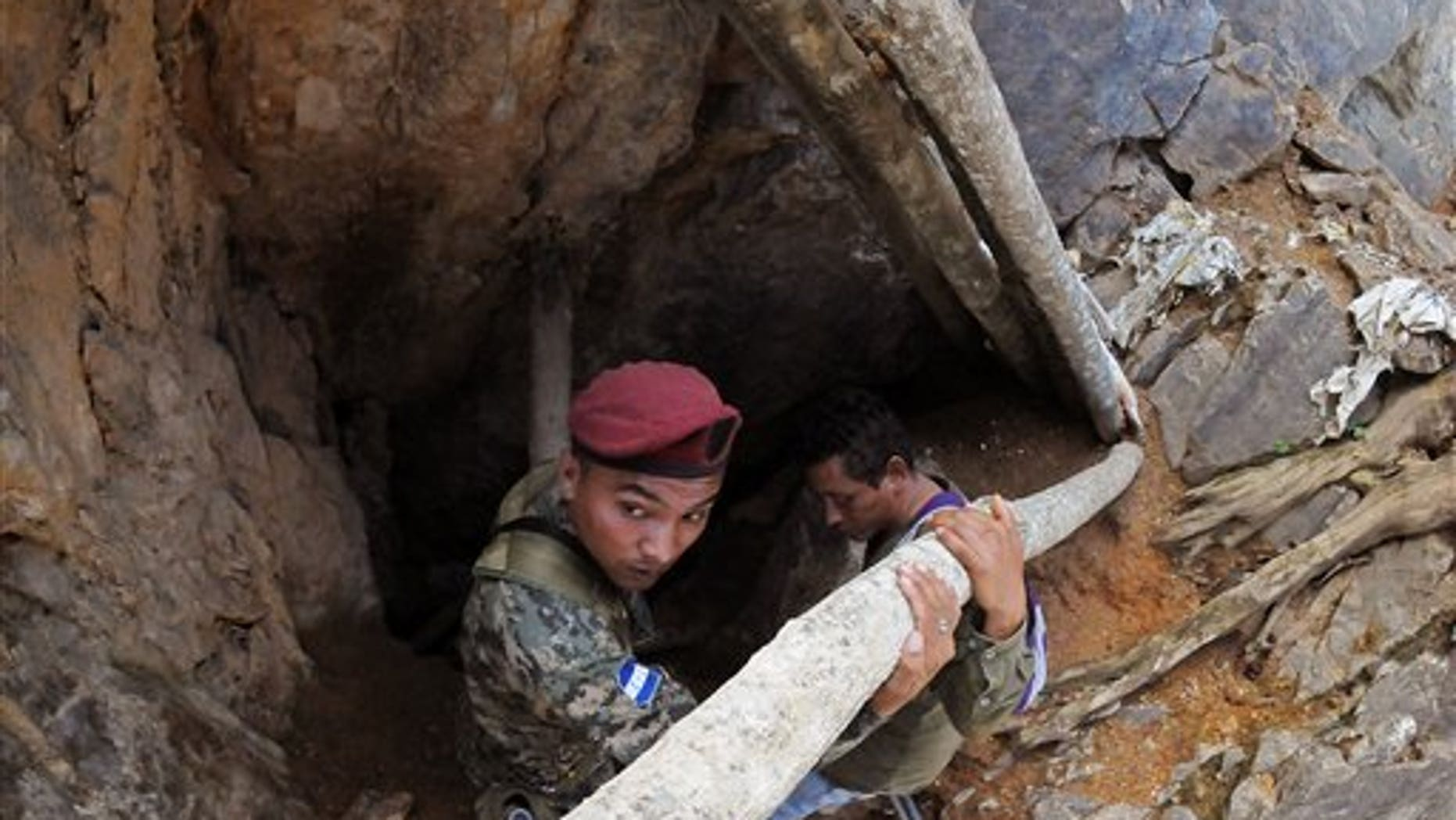 A soldier stands guard at the entrance of a collapsed gold mine where miners are trapped in San Juan Arriba, Choluteca in southern Honduras, Friday, July 4, 2014. Three miners were rescued Friday after spending more than two days trapped following a collapse at a small, wildcat gold mine. Eight others remain missing. (AP Photo/Fernando Antonio)