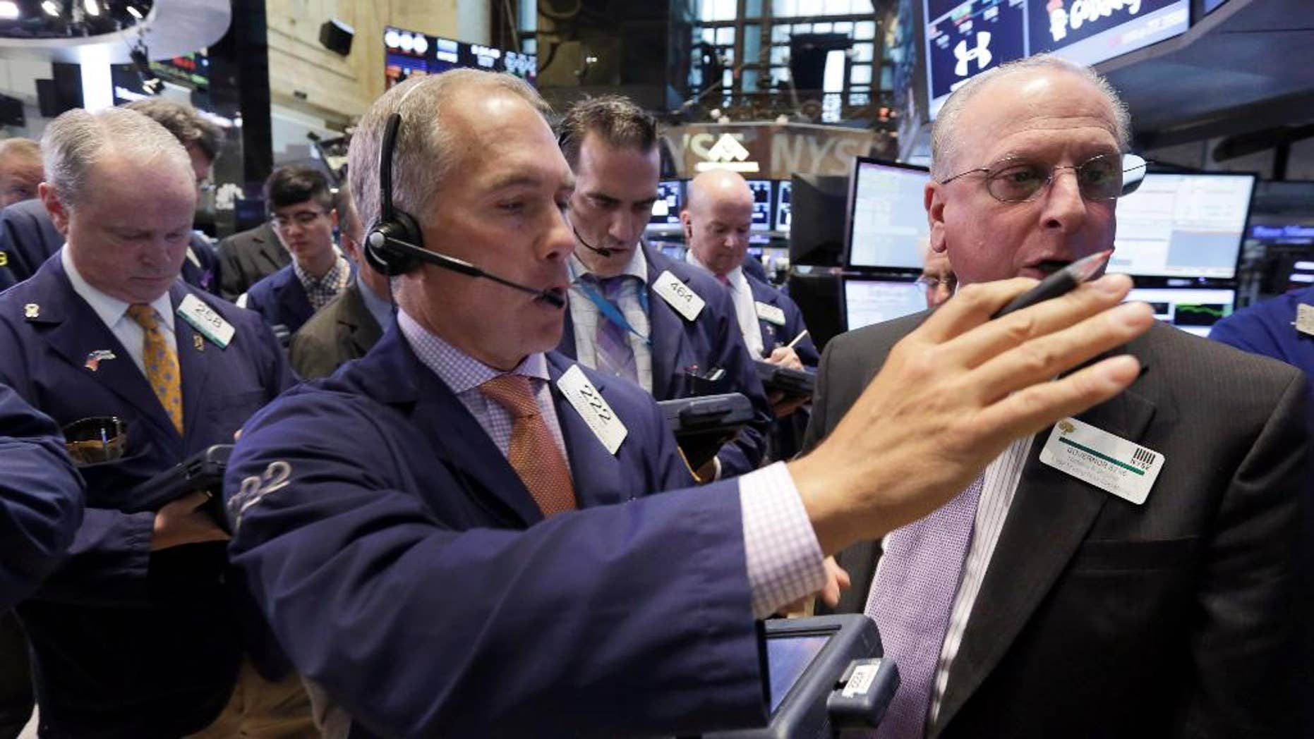 Trader Timothy Nick, center, works on the floor of the New York Stock Exchange, Tuesday, May 12, 2015. A key borrowing rate shot to a five-month high Tuesday morning, as traders around the world continued to sell off big government bonds. (AP Photo/Richard Drew)