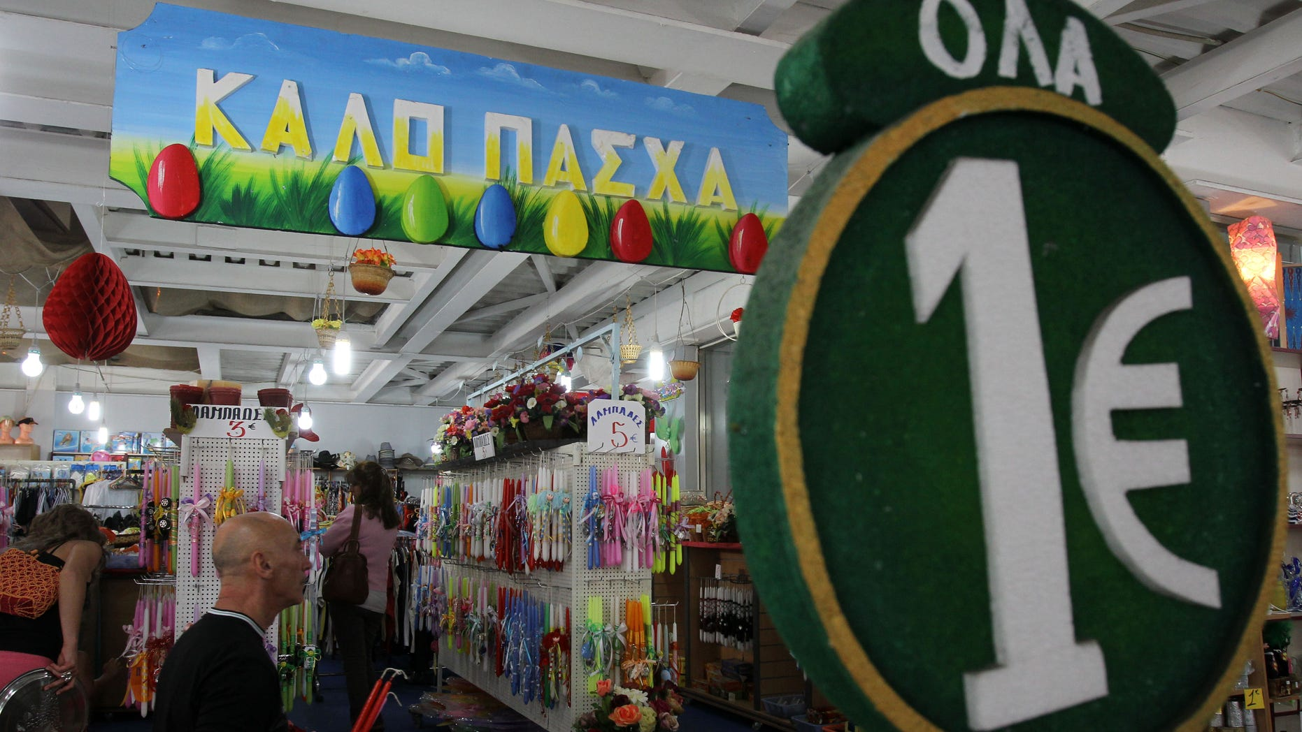 """A one-euro sign and a banner reading """"Happy Easter"""" are displayed at a discount store selling candles and other items at the start of Orthodox Holy Week, in Athens, Monday, April 29, 2013. Orthodox Christians around the world celebrate Easter on Sunday, May 5. Retailers and travel agents booking domestic trips are expecting slower sales over the Easter holidays, with a continued recession expected to see Greece's crisis-hit economy contract a further 4.25 percent this year. (AP Photo/Thanassis Stavrakis)"""