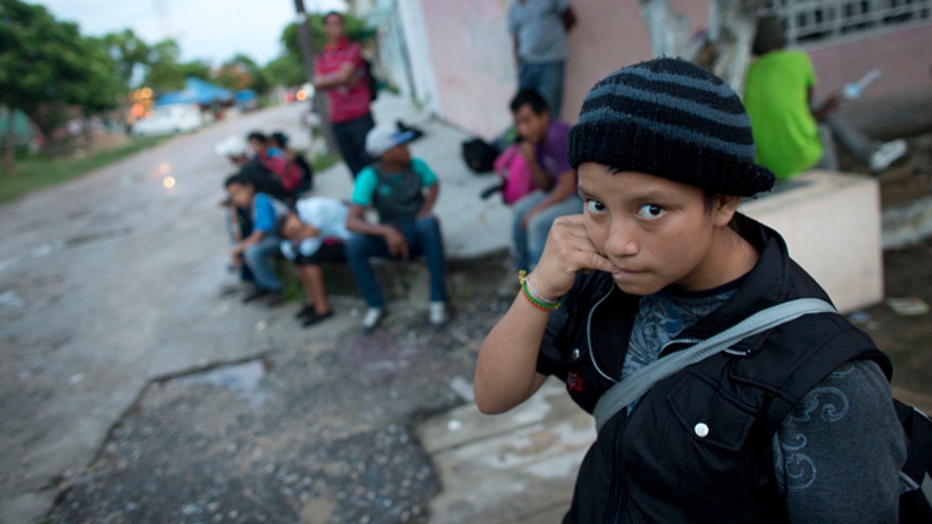 In this June 19, 2014 photo, a 14-year-old Guatemalan girl traveling alone waits for a northbound freight train along with other Central American migrants, in Arriaga, Chiapas state, Mexico. The United States has seen a dramatic increase in the number of Central American migrants crossing into its territory, particularly children traveling without any adult guardian. More than 52,000 unaccompanied children have been apprehended since October. (AP Photo/Rebecca Blackwell)