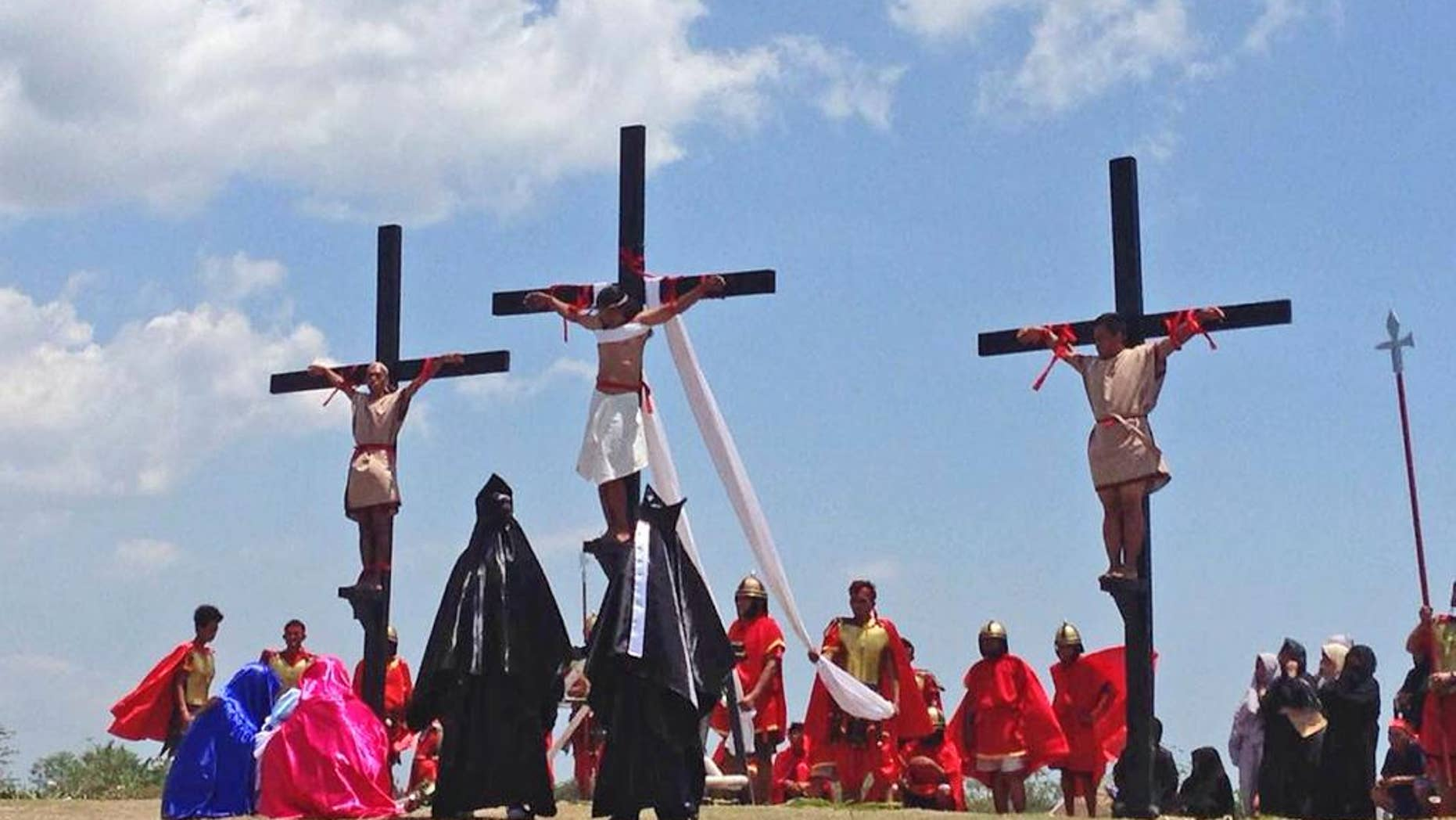 Filipino penitents on wooden crosses take part in a reenactment during Good Friday rituals on Friday, April 14, 2017 at Cutud, Pampanga province, northern Philippines. They were remembering Jesus Christ's suffering and death. (AP Photo/Vicente Gonzales)
