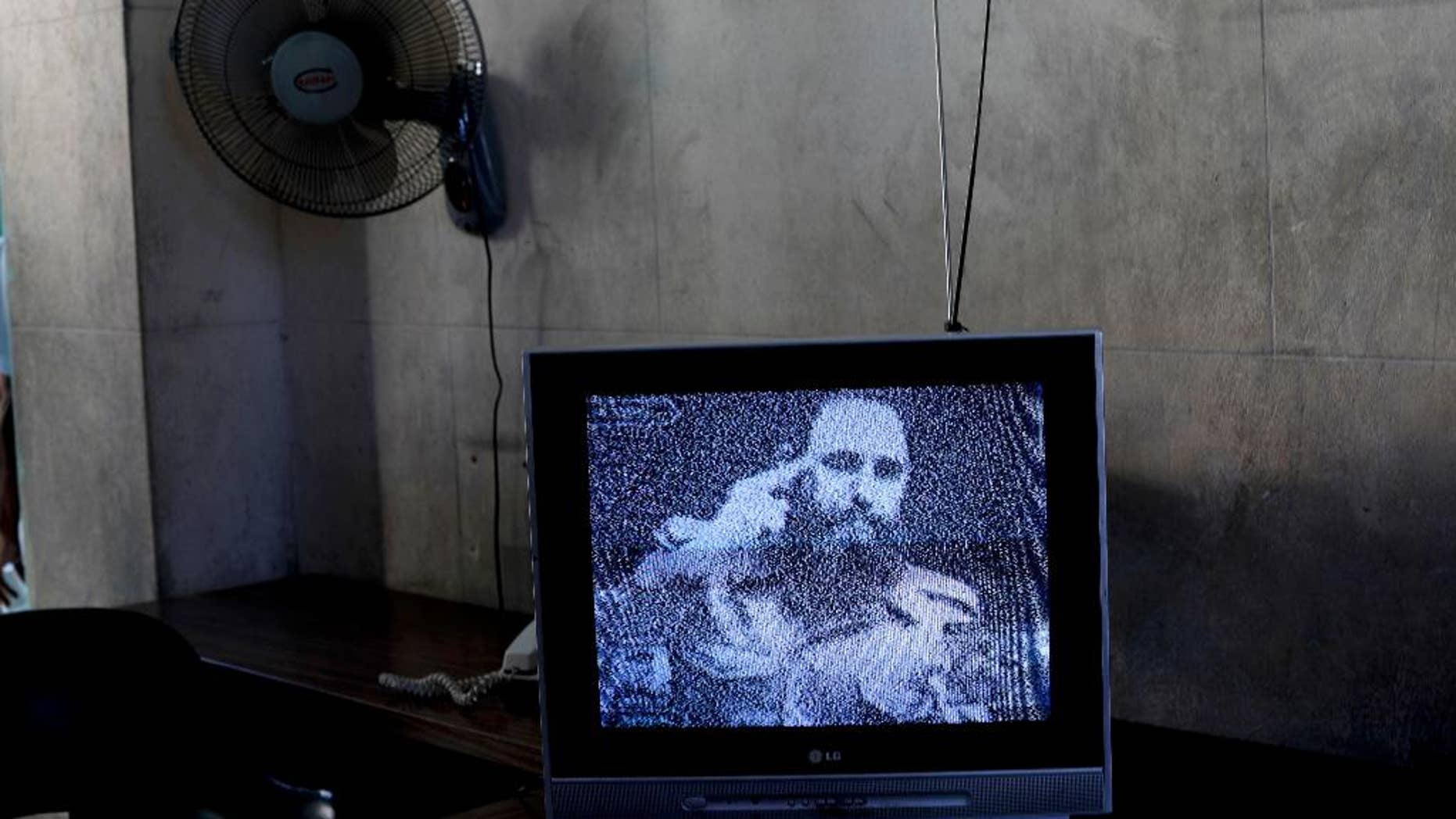 FILE - This Nov. 29, 2016 file photo shows a television broadcasting black and white footage of Fidel Castro at a memorial in his honor in Guanabacoa, on the outskirts of Havana, Cuba. With a shaking voice, President Raul Castro announced on state television that his older brother died Friday evening, Nov. 25. He was 90.  (AP Photo/Natacha Pisarenko, File)